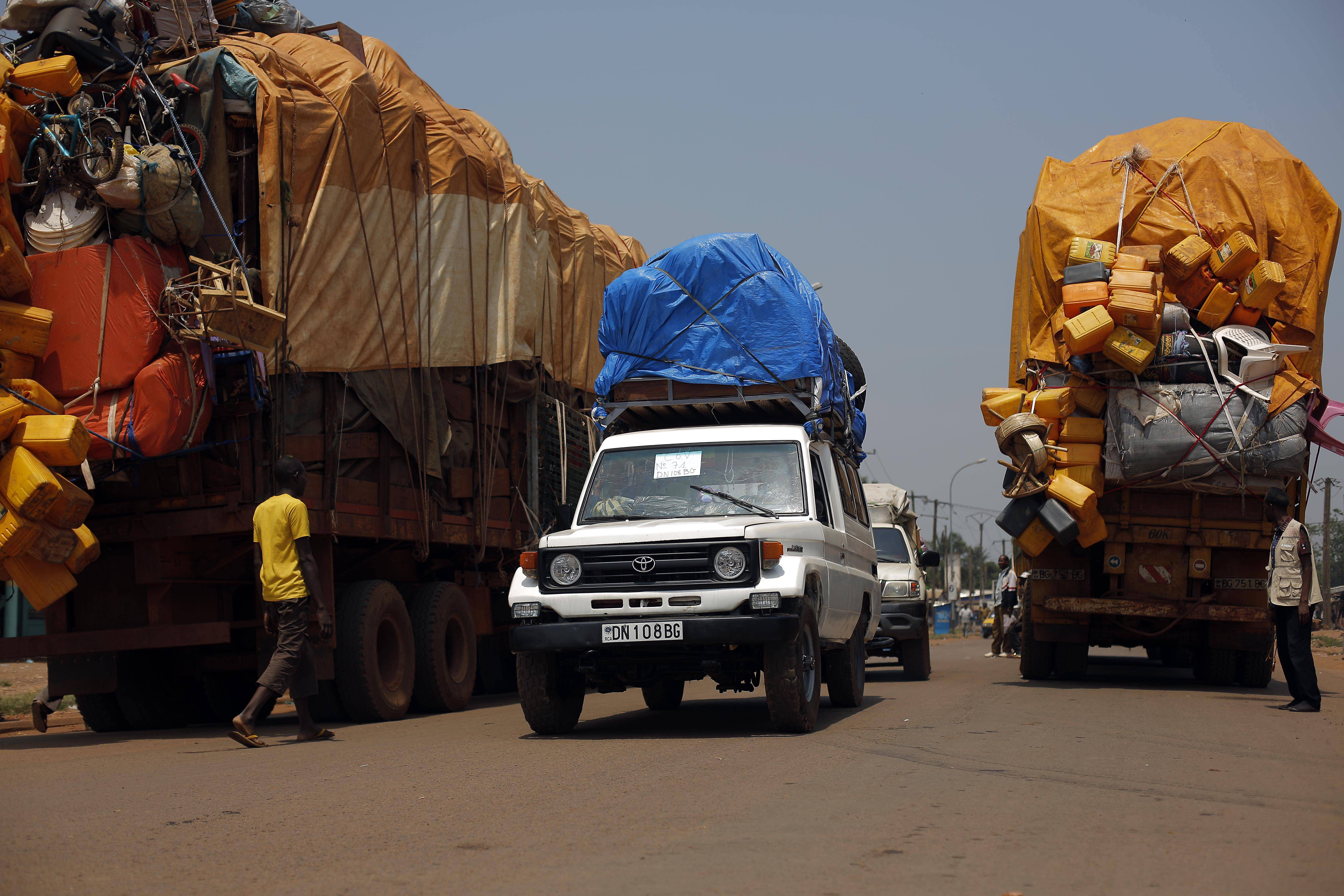 A convoy of more than 100 vehicles turns around Friday as Misca troops deem the road out was not secure, in Bangui, Central African Republic.