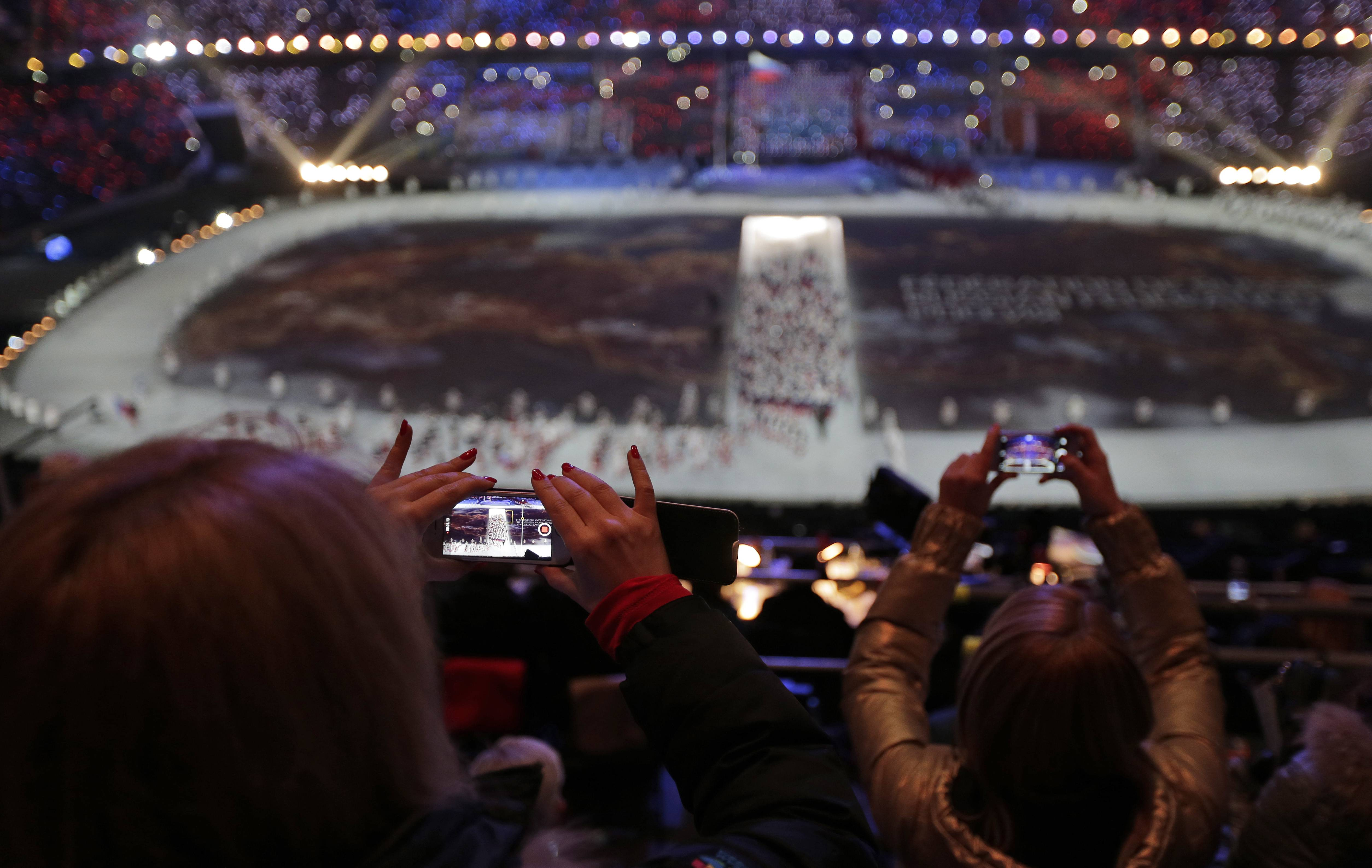 A spectator takes a video of the opening ceremony on her mobile phone at the 2014 Winter Olympics in Sochi, Russia.