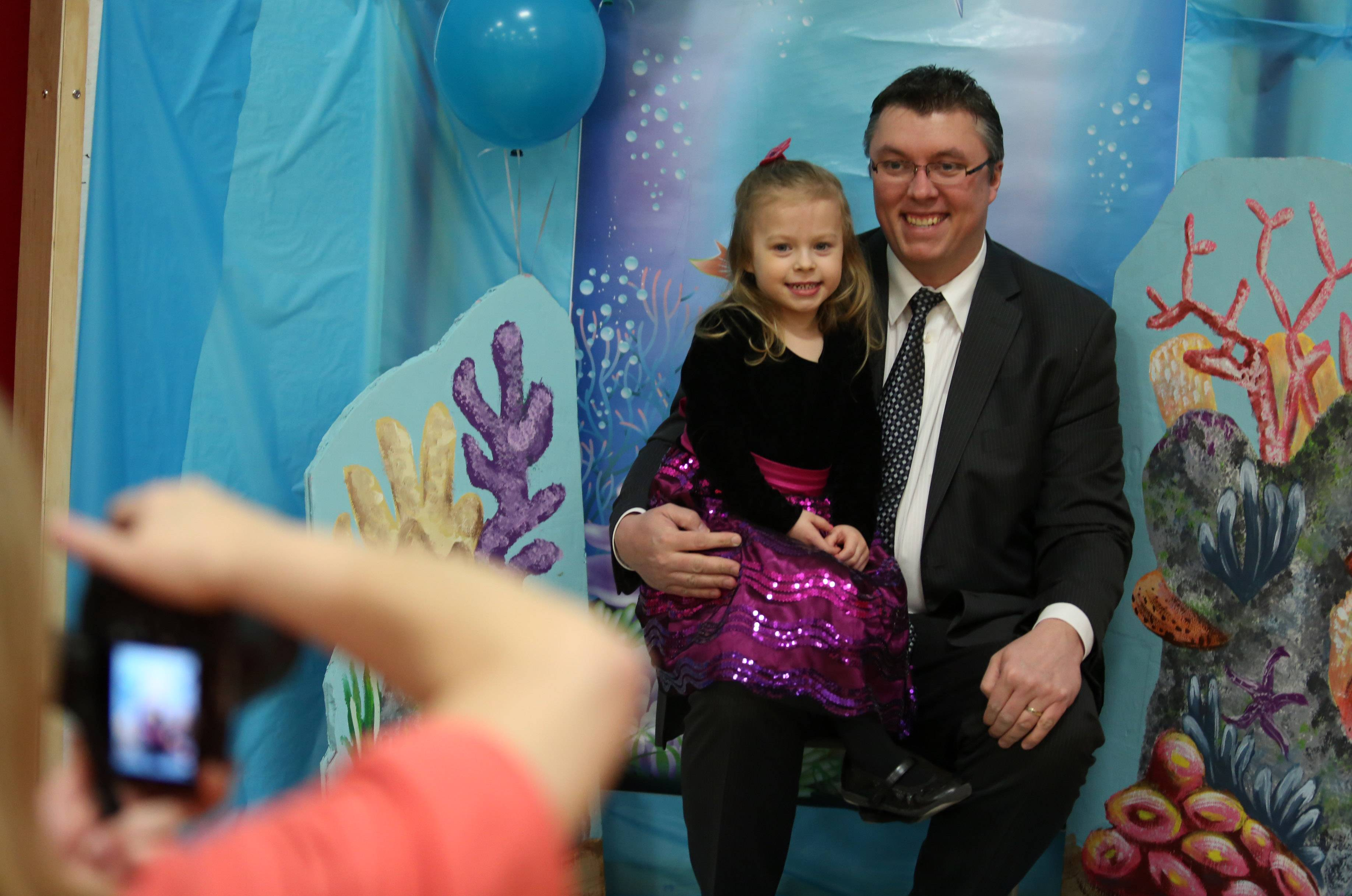 Martin Mularczyk of Schaumburg and his daughter Melania get their portrait taken at a dad and daughter dance at the Community Recreation Center on Saturday night in Schaumburg.