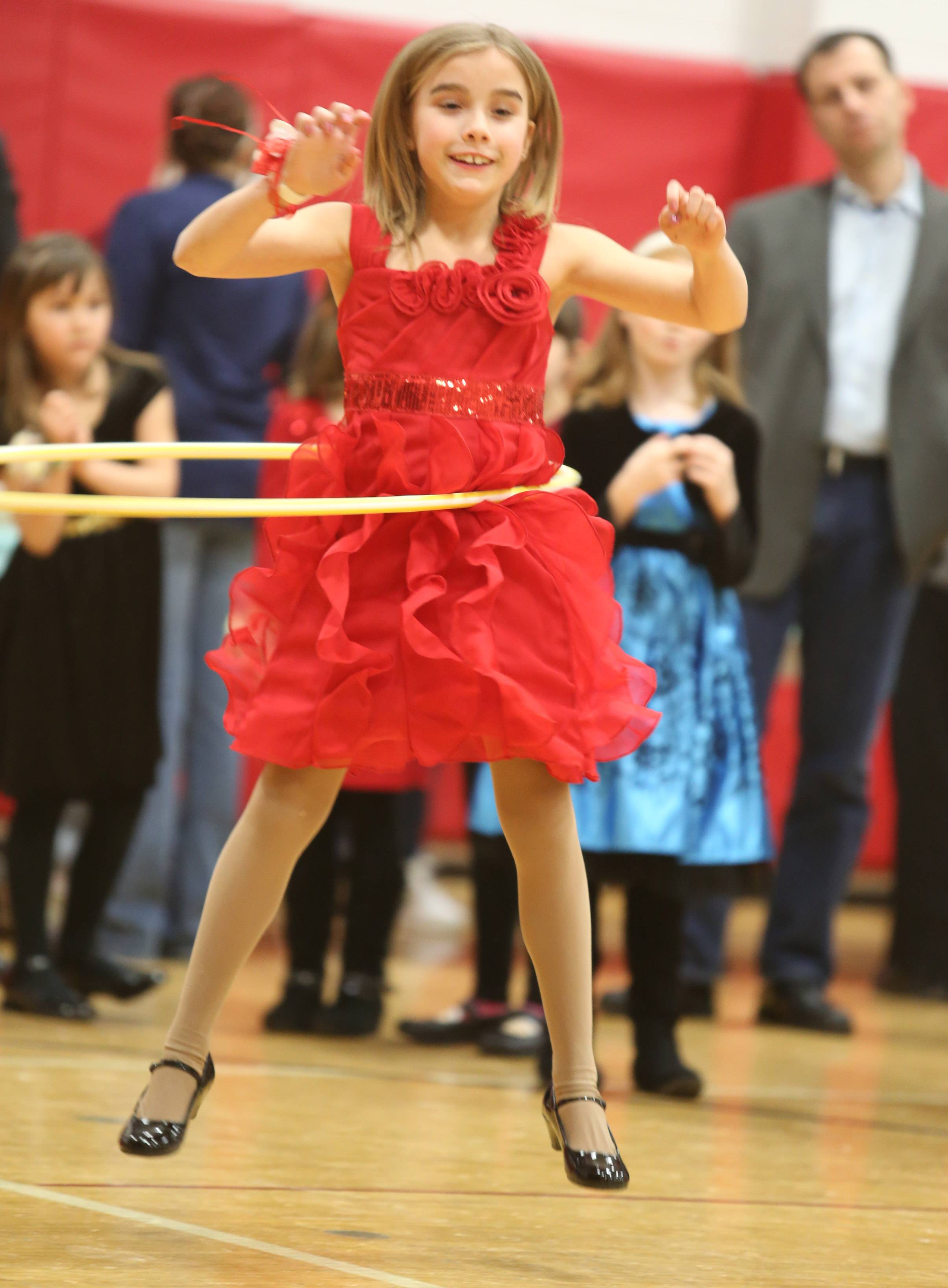 Gracie Carey, 8, of Schaumburg, competes in a hula-hoop contest at a dad and daughter dance at the Community Recreation Center on Saturday night in Schaumburg.