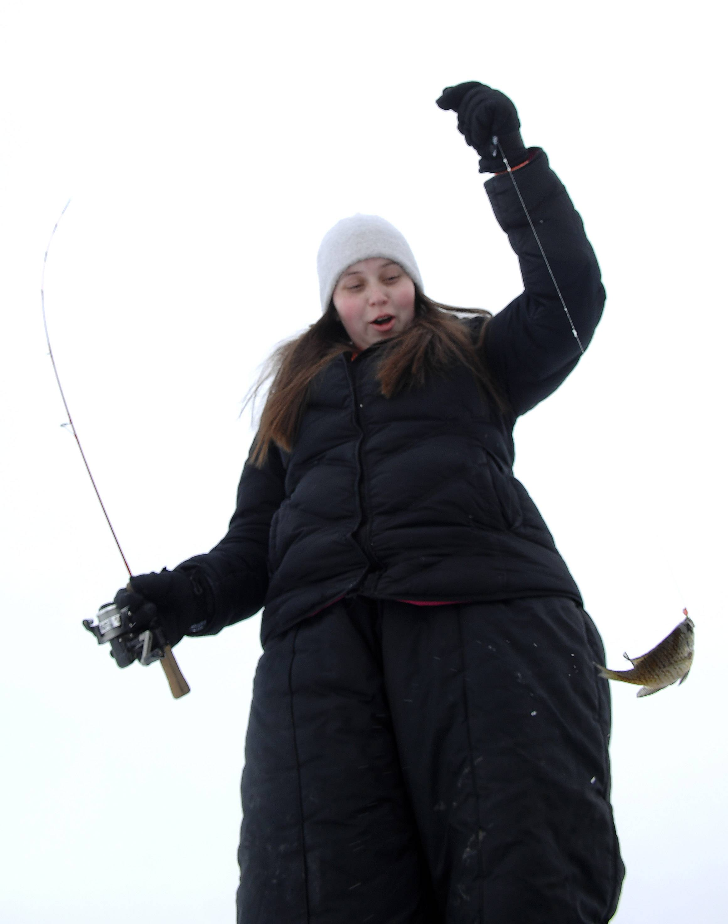 Noel Hoger, 17, of Algonquin pulls in a little bluegill while ice fishing at Lake Atwood in The Hollows Conservation Area during a park district-sponsored event in Cary Saturday. Aside from making holes and providing poles, the park district also shared tips for safe ice fishing.