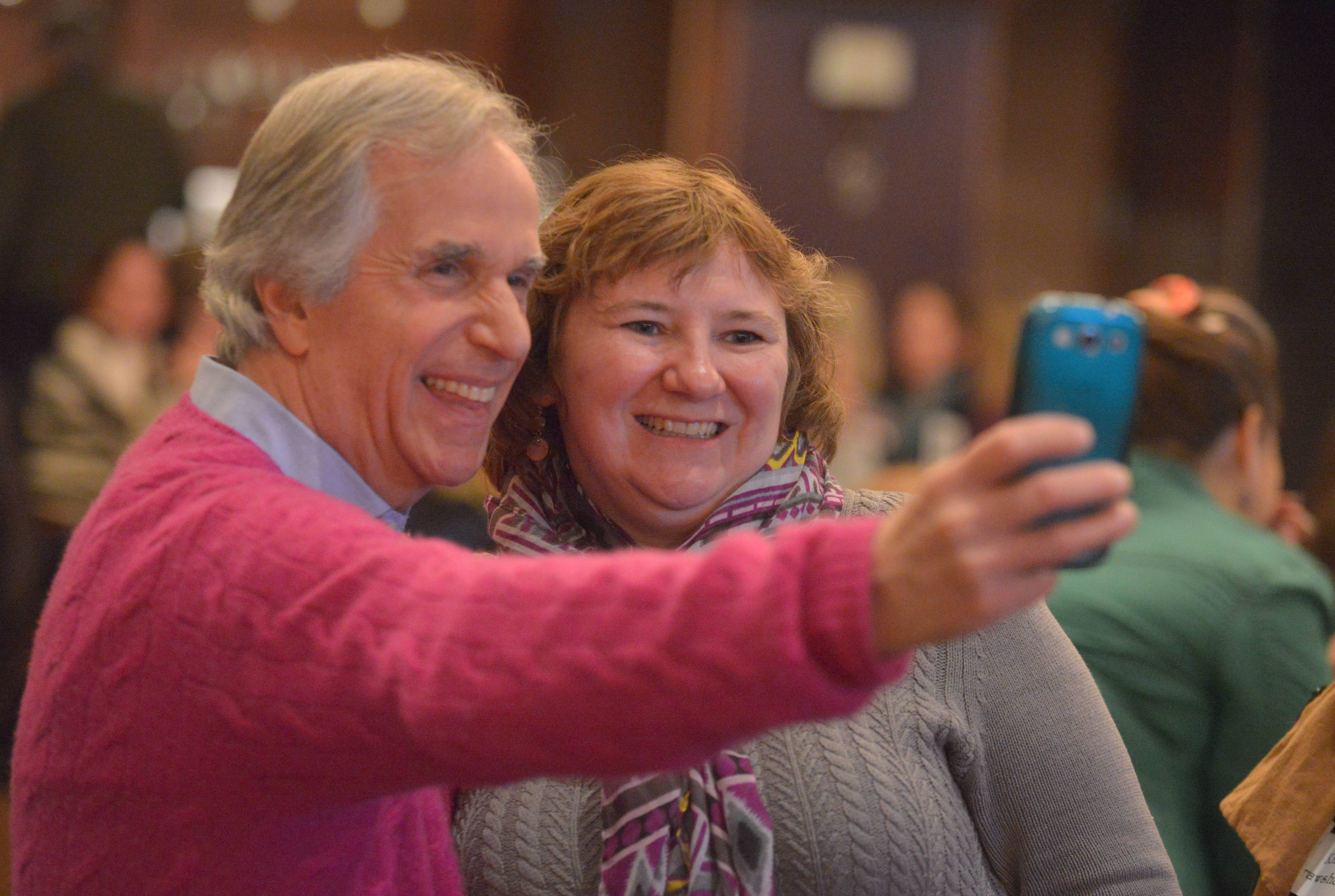 "Henry Winkler, who played the Fonz on the TV show ""Happy Days"" snaps a self-portrait with Ginny Sieck of Geneva, who was one of more than 500 people gathered Saturday in Woodridge to hear Winkler discuss his new children's book series ""Here's Hank."" Winkler and his writing partner, Lin Oliver, were among six keynote speakers during Naperville-based Anderson's Bookshop's annual Children's Literature Breakfast."