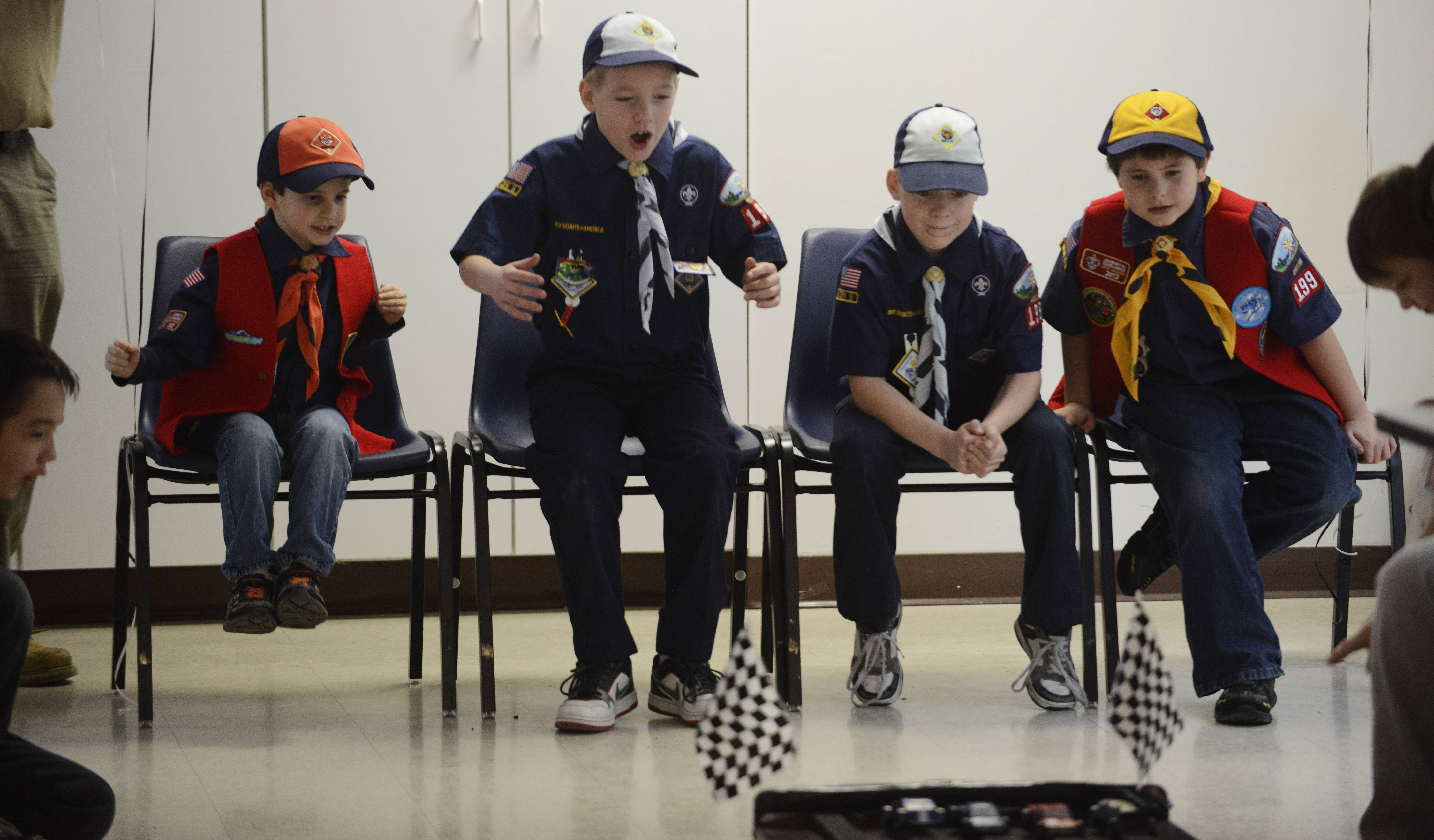 Left to right, Cadyn Wollmuth, 6, twins Brayden and Bryan O'Connor, 8, and Lucas Wollmuth, 8, cheer as the four fastest cars compete Saturday during the Cub Scout Super Pack 199 annual Pinewood Derby at the Round Lake Area Park District's Robert W. Rolek Community Center.