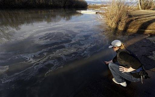 Amy Adams, North Carolina campaign coordinator with Appalachian Voices dips her hand into the Dan River in Danville, Va. as signs of coal ash appear in the river.