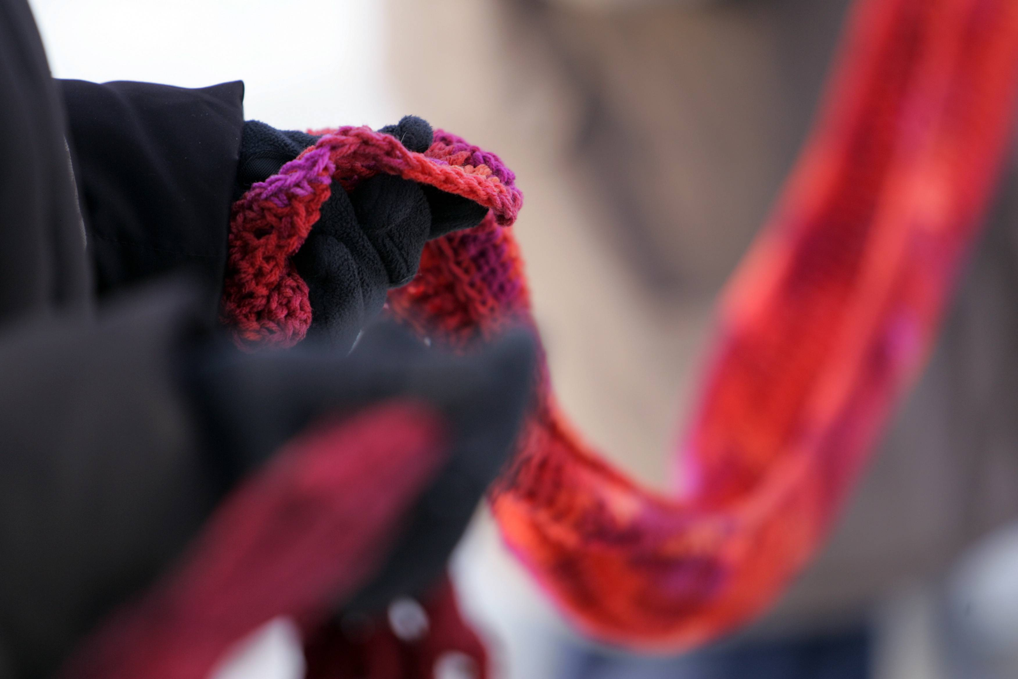 "About 110 people came together at the Gail Borden Public Library in Elgin and formed a line while holding red scarves as part of the ""One Billion Rising"" global campaign to end violence against women and girls. Later, violence survivors shared their stories."