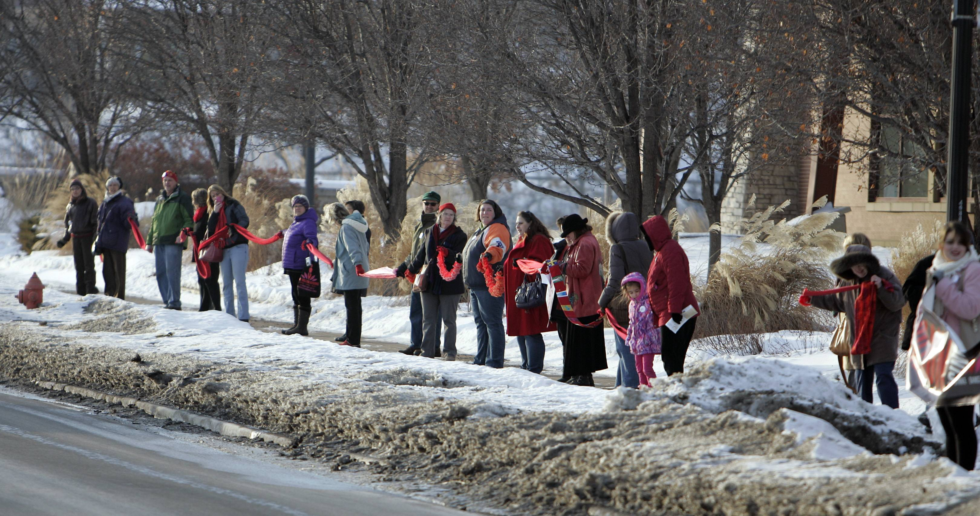 "About 110 people lined Kimball Street, pictured, and Grove Street on Friday at the Gail Borden Public Library in Elgin. They formed a line while holding red scarves, as part of the ""One Billion Rising"" global campaign to end violence against women and girls."