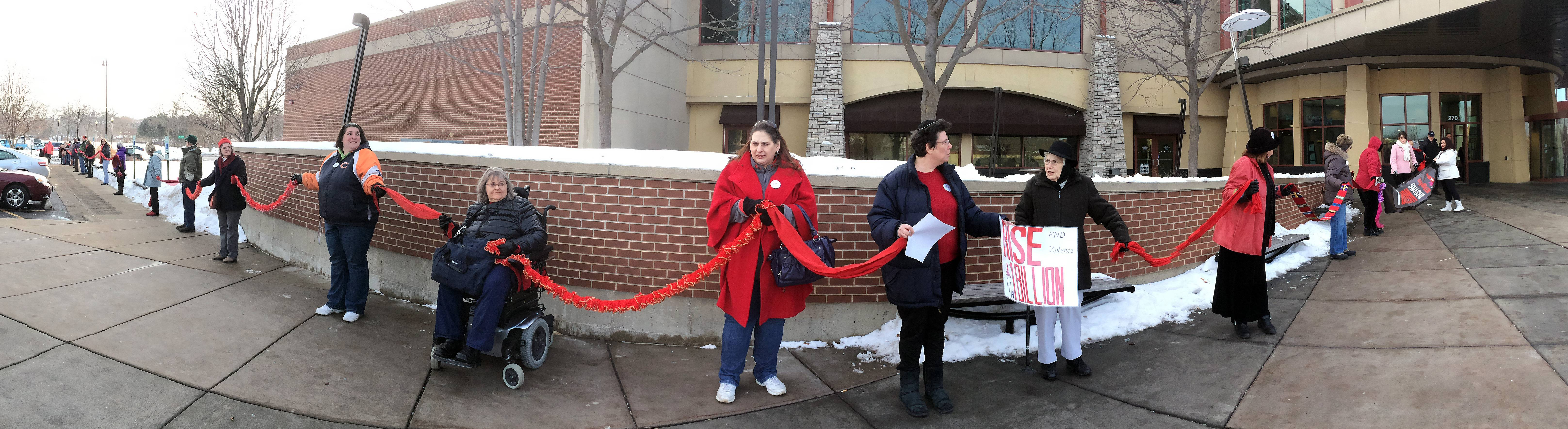 "About 110 people came together Friday at the Gail Borden Public Library in Elgin and formed a line while holding red scarves as part of the ""One Billion Rising"" global campaign to end violence against women and girls."