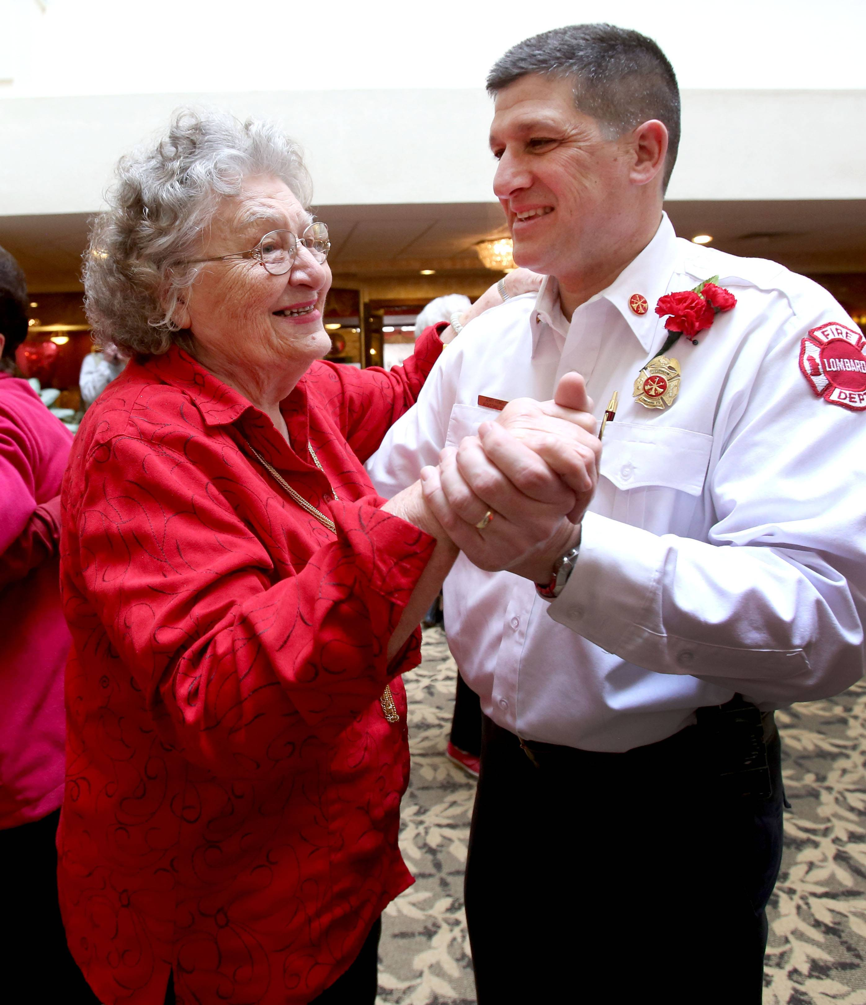 Lillian Mastro dances with Assistant Fire Chief Jerry Howell at a Valentine's Day dance at Lexington Square senior center Friday in Lombard.