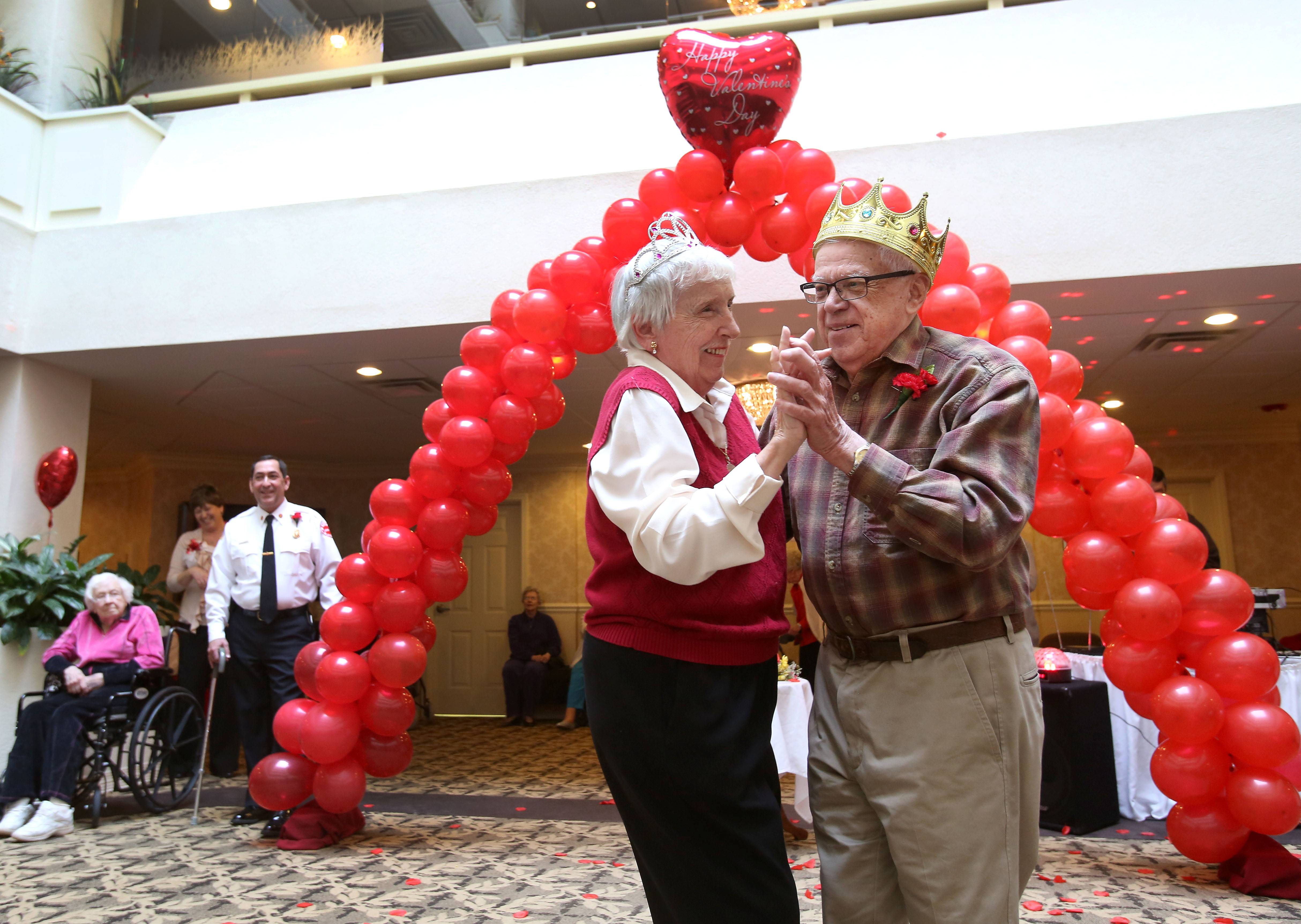 Lombard Fire Chief Paul Dirienzo, left, looks on as Ray Knable and Joanne Campbell, crowned king and queen of the Valentine's Day Dance, take to the floor at Lexington Square senior center in Lombard.