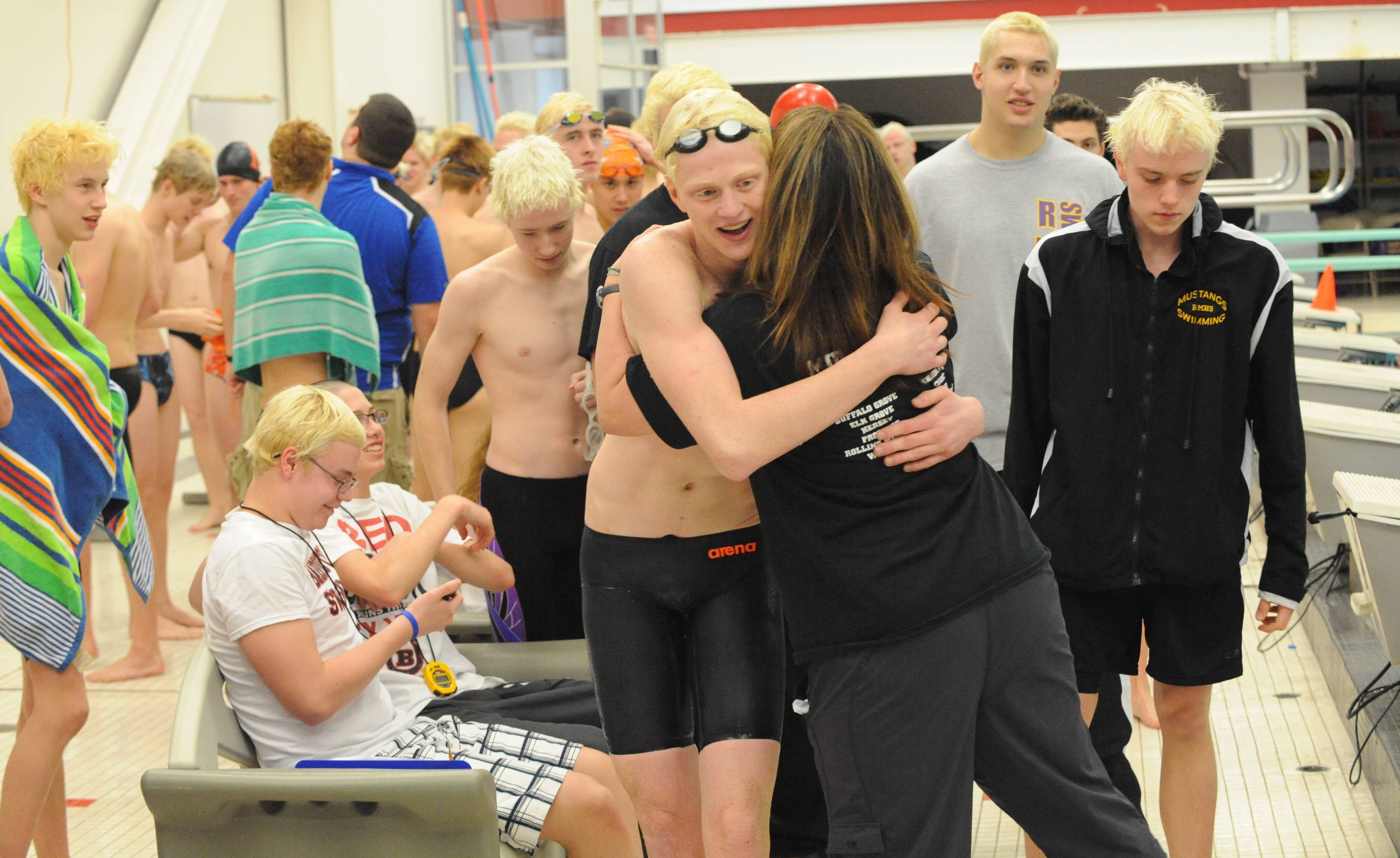 Rolling Meadows junior Jake Barson, left, and coach Monika Chiappetta hug it out after Barson's victory in the 100-yard breaststroke in Saturday's MSL meet.