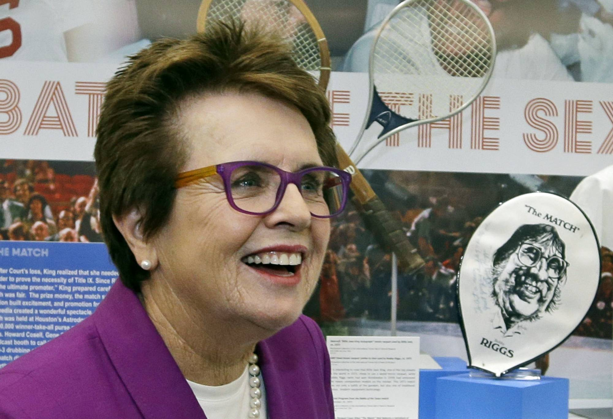 In this Sept. 5, 2013, file photo, Billie Jean King reflects about her match against Bobby Riggs in 1973 as she stands in front of a display at the U.S. Open tennis tournament in New York. King, who couldn't attend the opening of the Sochi Olympic Games because of her mother's death, will attend the closing ceremony with American speed skaters Bonnie Blair and Eric Heiden on Feb. 23 as part of President Barack Obama's official U.S. delegation.