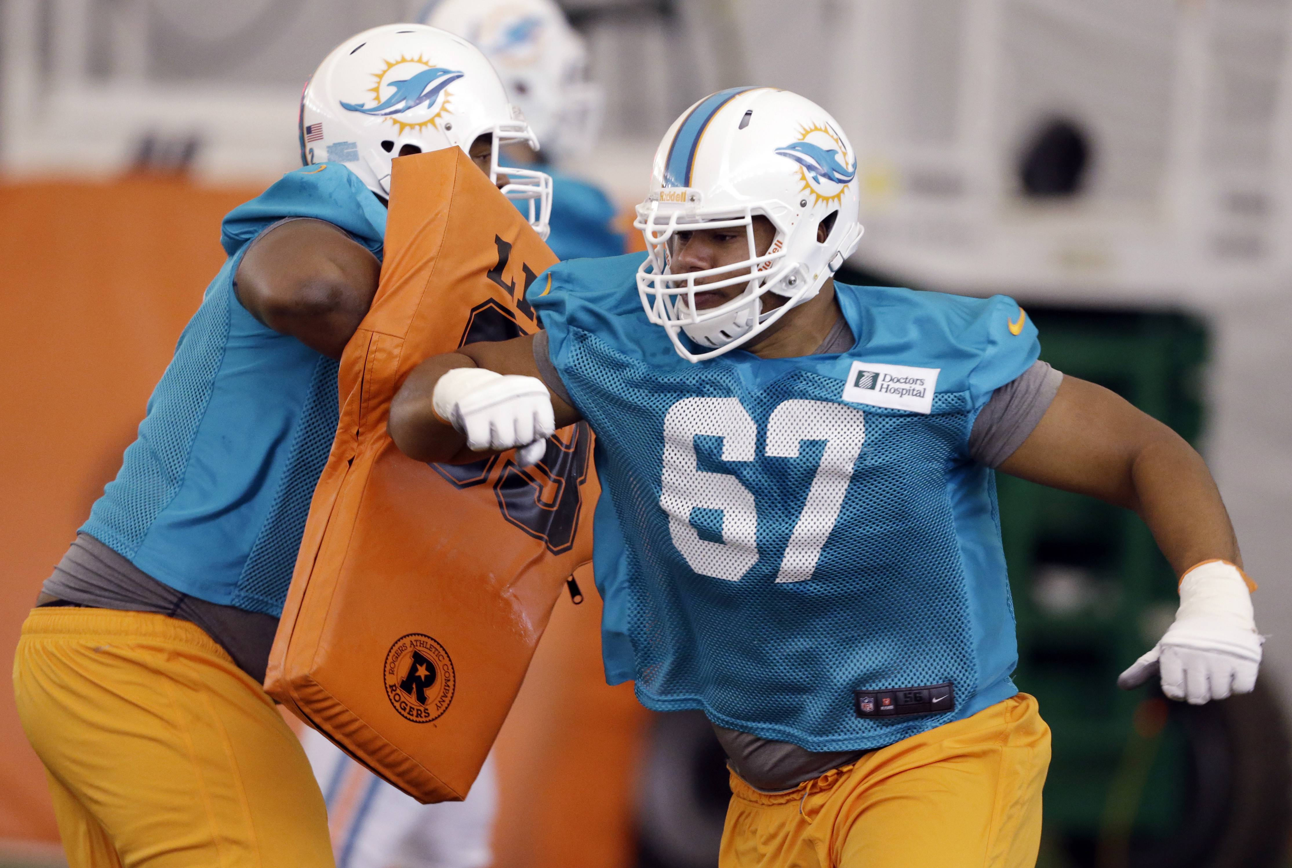"In this July 21, 2013, file photo, Miami Dolphins tackle Andrew McDonald (67) works on a drill with offensive guard Chris Barker during an NFL football practice at the NFL football team's training facility in Davie, Fla. McDonald's agent says the former Dolphins lineman, identified as Player A in the investigation of the racially charged bullying scandal, is ""disappointed his name has ""become associated with other players involved this story."""