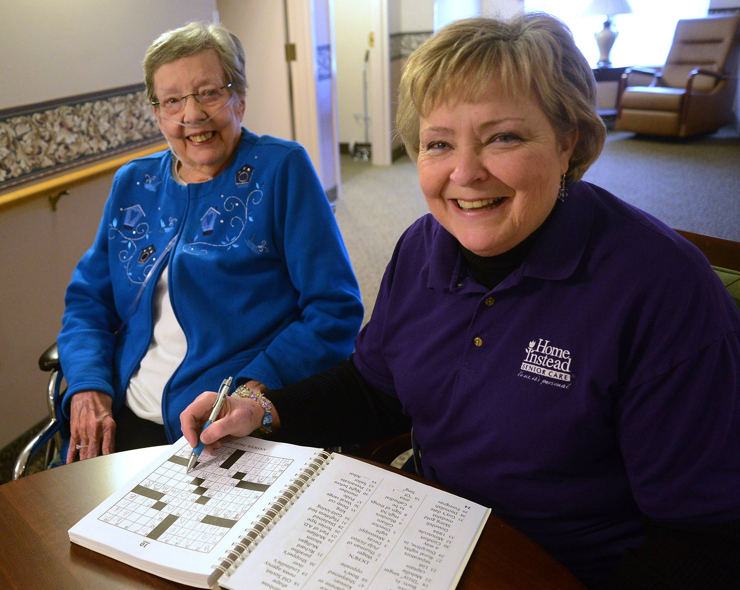 Caregiver Terrie Thompson, right, works a crossword puzzle with client Ann Stillwaugh.