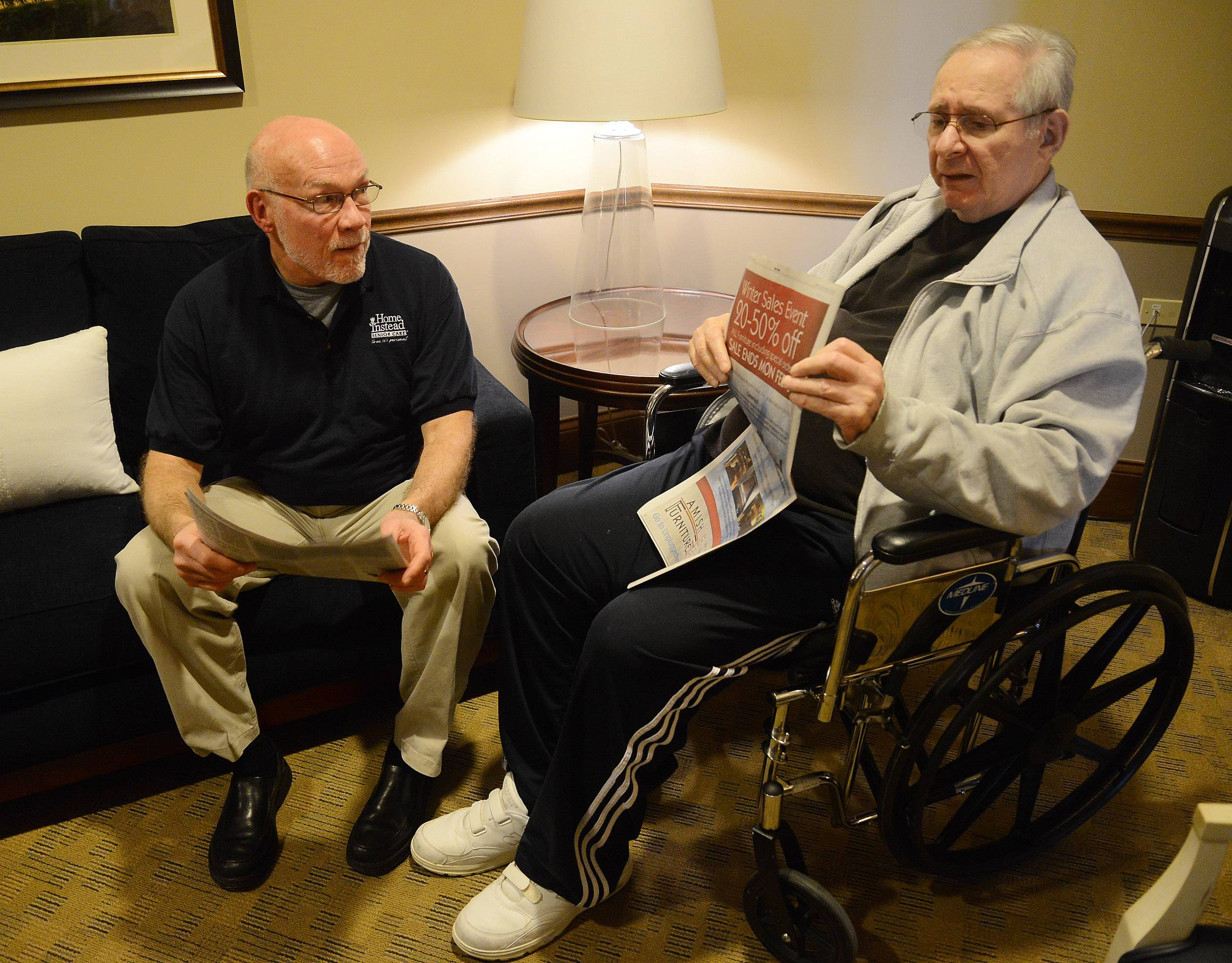 Caregiver Bruce Cruz, left, from Home Instead spends time with his client, Jerry Miller, reading the newspaper together, which they often do.