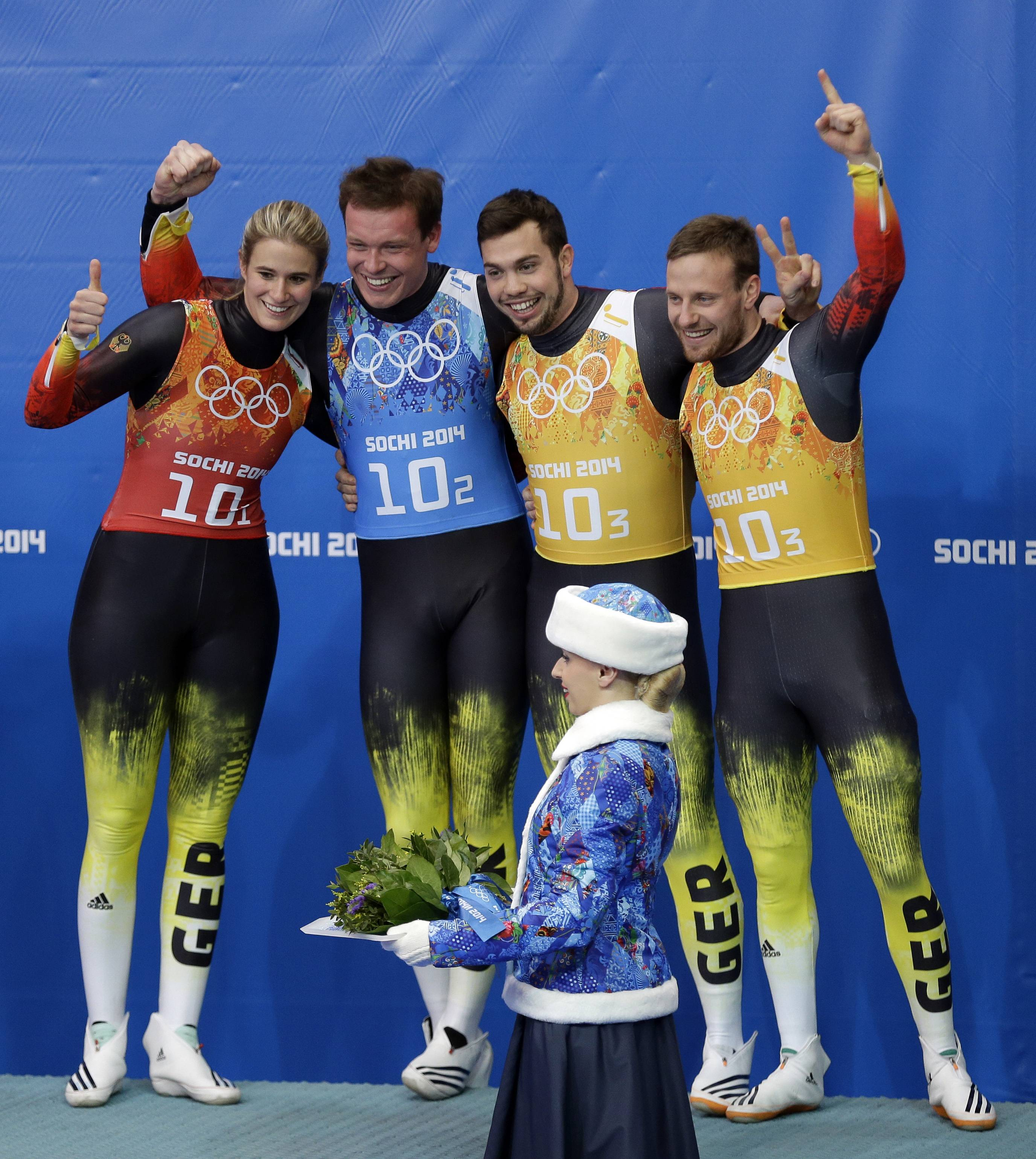 The German team of Natalie Geisenberger, in orange, Felix Loch, in blue, and doubles team of Tobias Wendl and Tobias Arlt, in yellow, wait for the flower ceremony to begin after winning the gold medal during the luge team relay competition at the 2014 Winter Olympics, Thursday, Feb. 13, 2014, in Krasnaya Polyana, Russia.