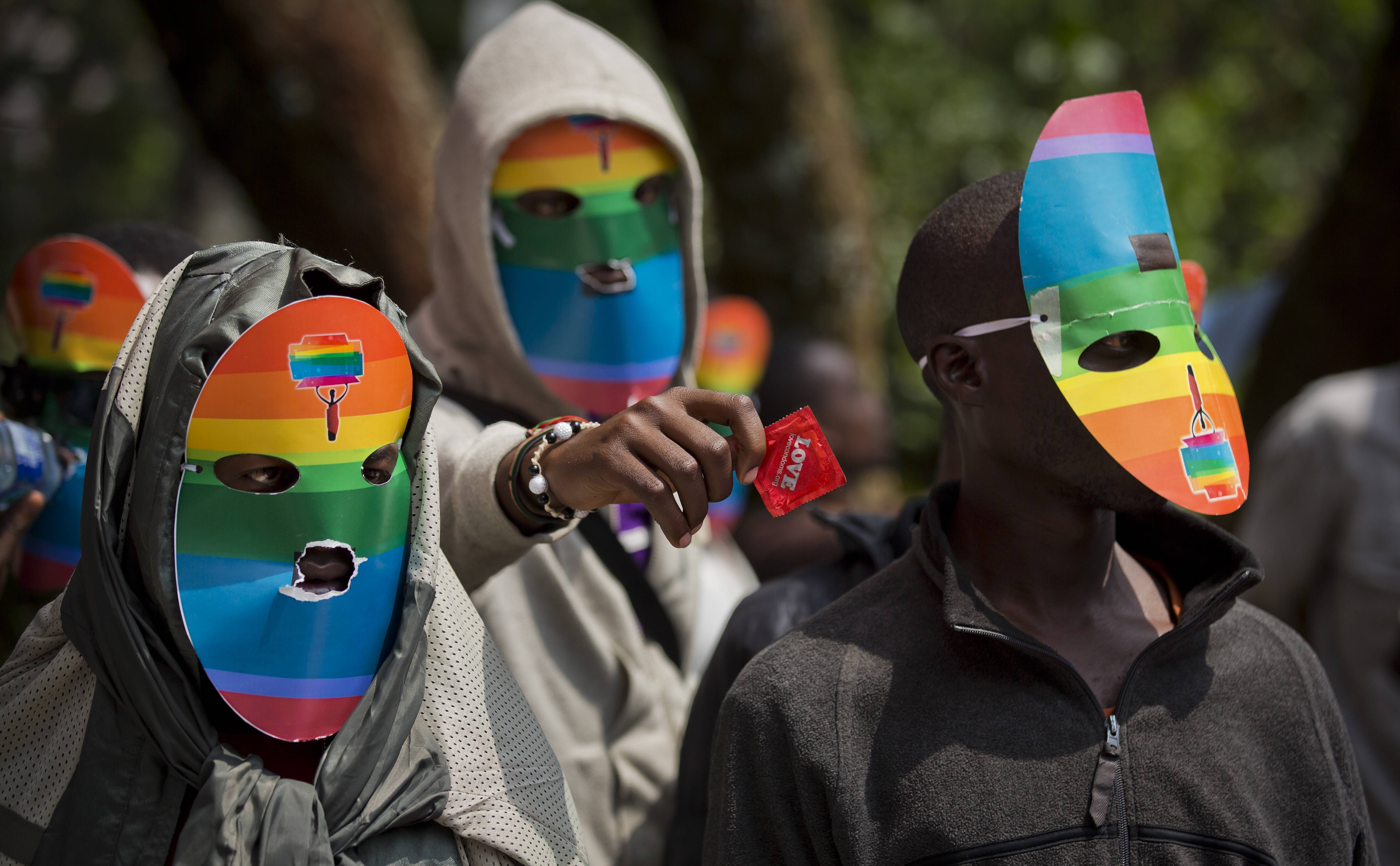 "In a Monday, Feb. 10 file photo, Kenyan gays and lesbians and others supporting their cause wear masks to preserve their anonymity and one holds out a wrapped condom, as they stage a rare protest, against Uganda's increasingly tough stance against homosexuality in solidarity with their counterparts there, outside the Uganda High Commission in Nairobi, Kenya. President Barack Obama says in a statement provided Sunday that pending steps by Uganda to further criminalize homosexuality will complicate what he is describing as America's valued relationship with the East African nation. Museveni said Friday that he plans to sign a bill into law that prescribes life imprisonment for what they term as ""aggravated"" homosexual acts."