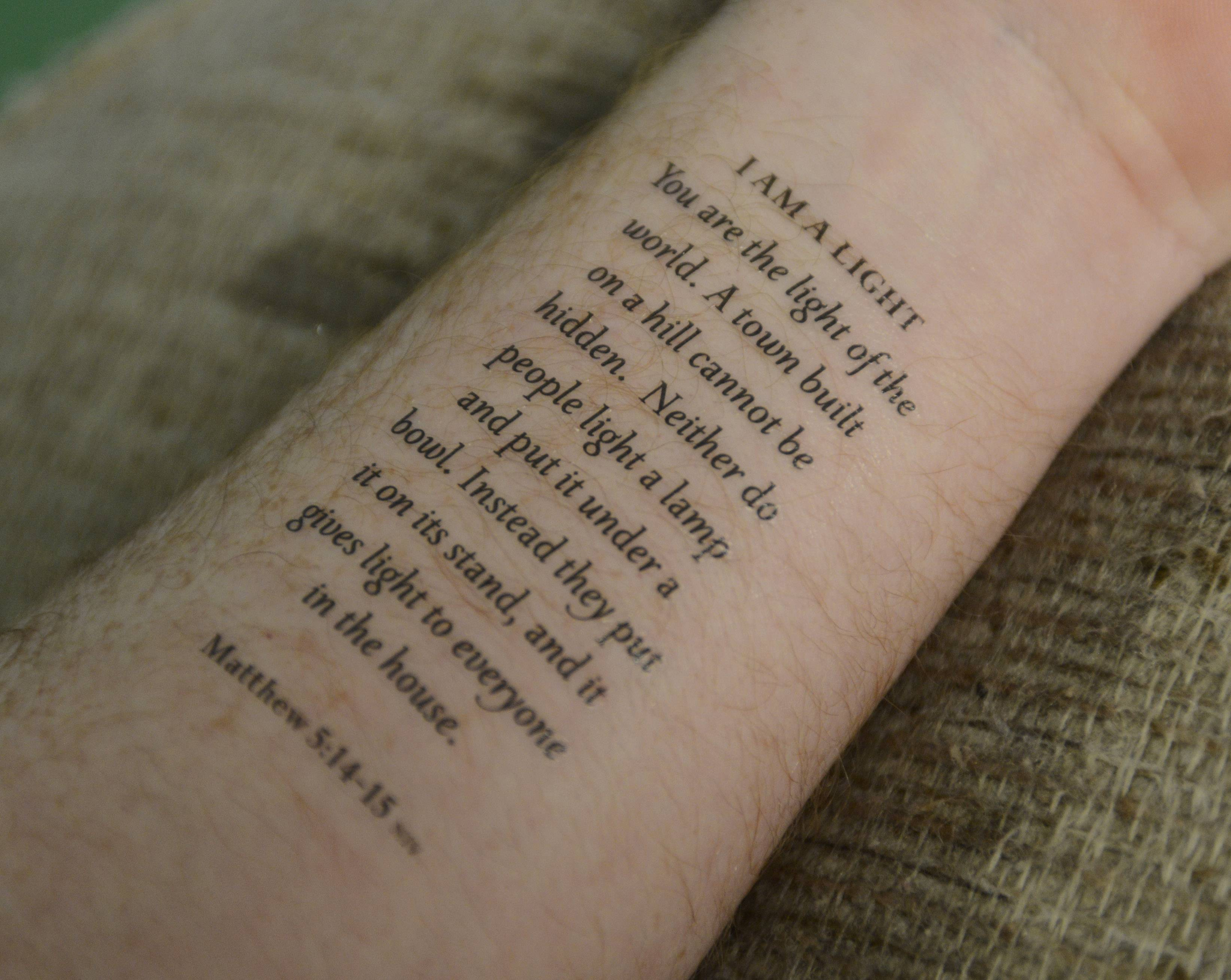 This temporary tattoo of a Biblical passage is on a person's forearm.
