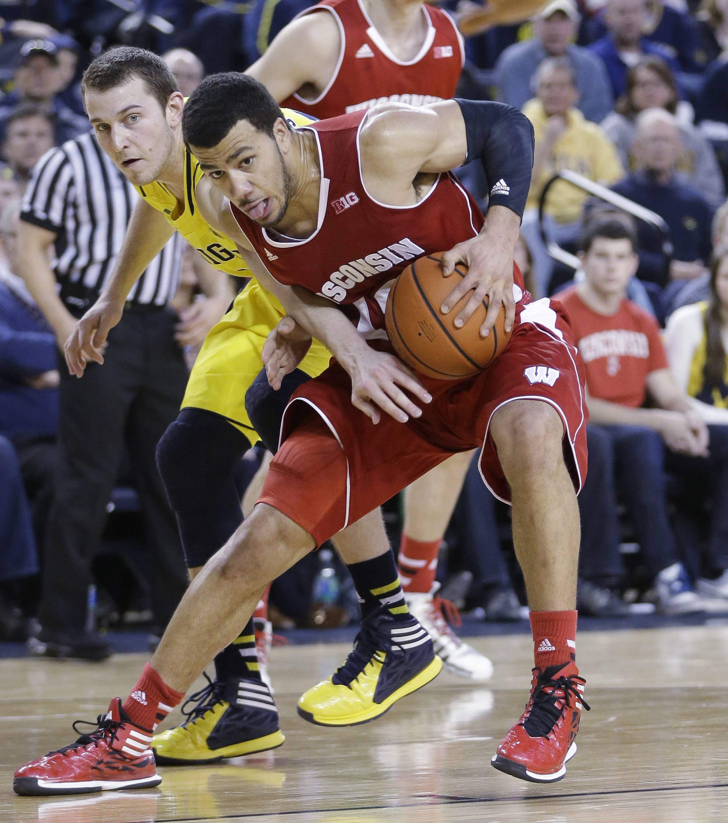 Michigan guard Nik Stauskas, left, reaches in on Wisconsin guard Traevon Jackson (12) during the second half of an NCAA college basketball game in Ann Arbor, Mich., Sunday, Feb. 16, 2014. Wisconsin defeated Michigan 75-62.