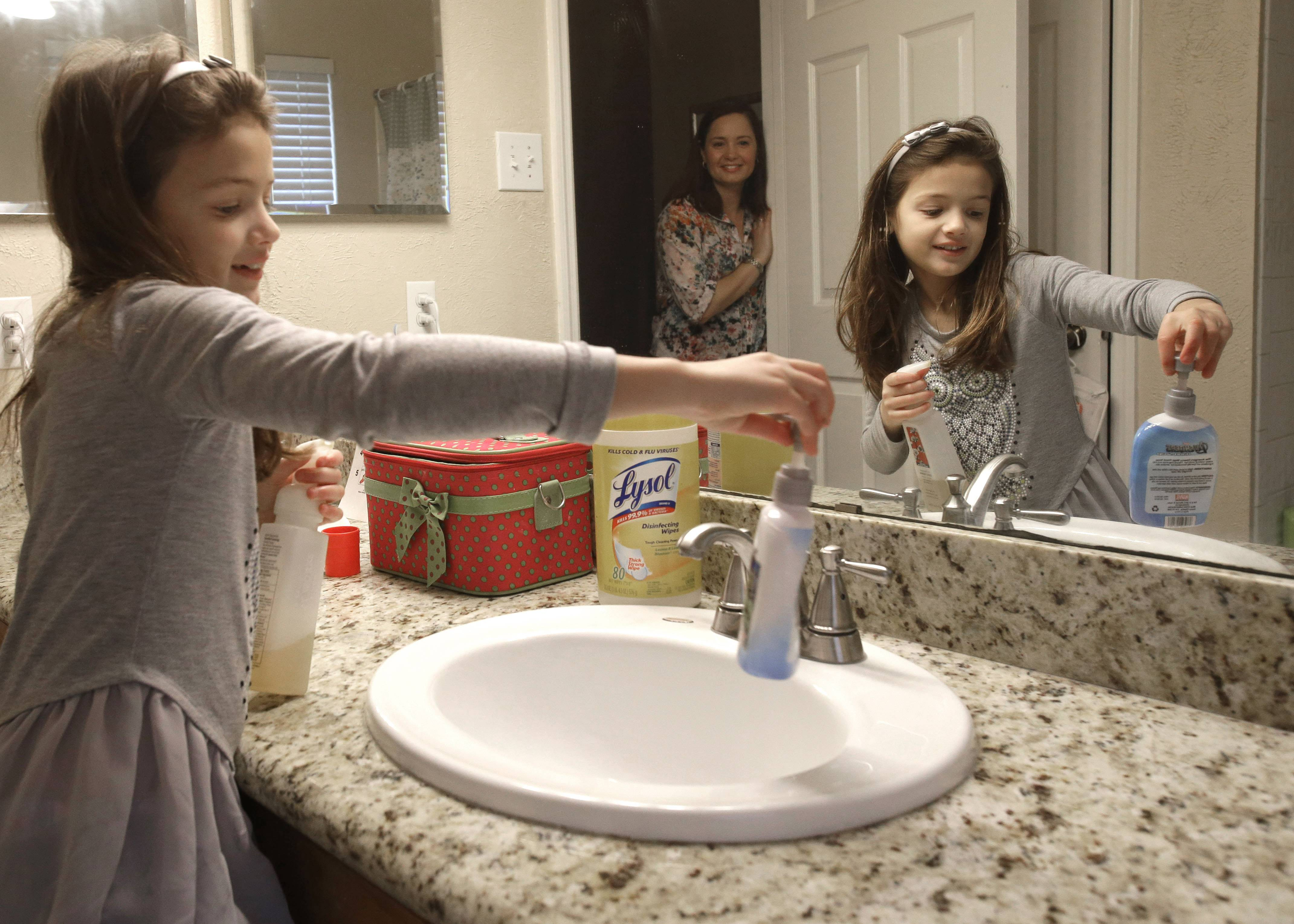 Lily Cherry, 8, cleans her bathroom as her mother, Andrea, supervises at their home in Kingwood, Texas. Cherry has passed on her childhood practice of doing chores to her own children believing it gives them a sense of family responsibility.