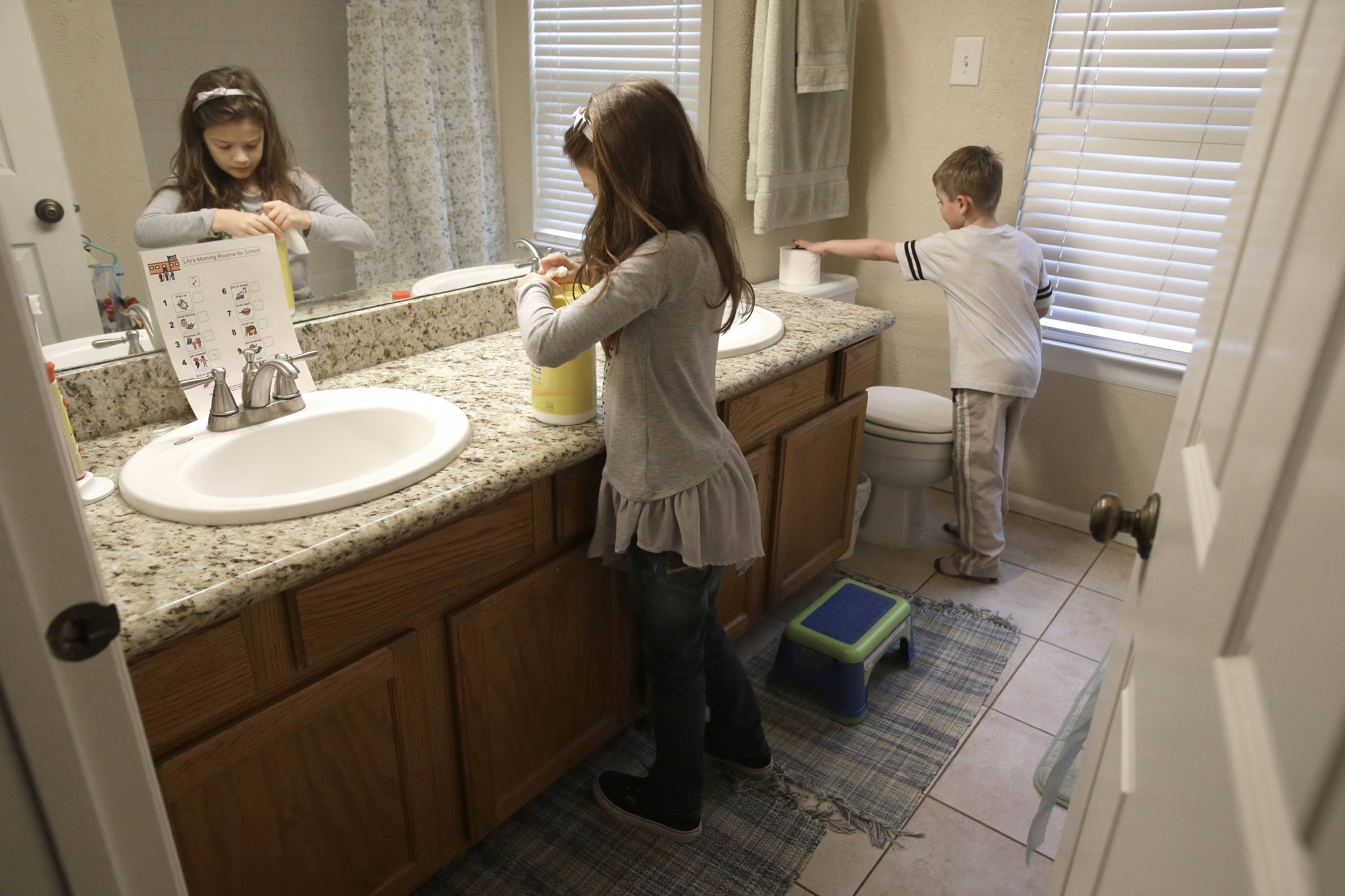Lily Cherry, 8, cleans her bathroom as her brother Aiden, 6, right, puts out a new roll of toilet paper at their home in Kingwood, Texas. For mother Andrea Cherry, who works full time, having the kids help makes it possible for her and her husband who would otherwise do all the cleaning, to have enough time to take the kids to their soccer practices and games.