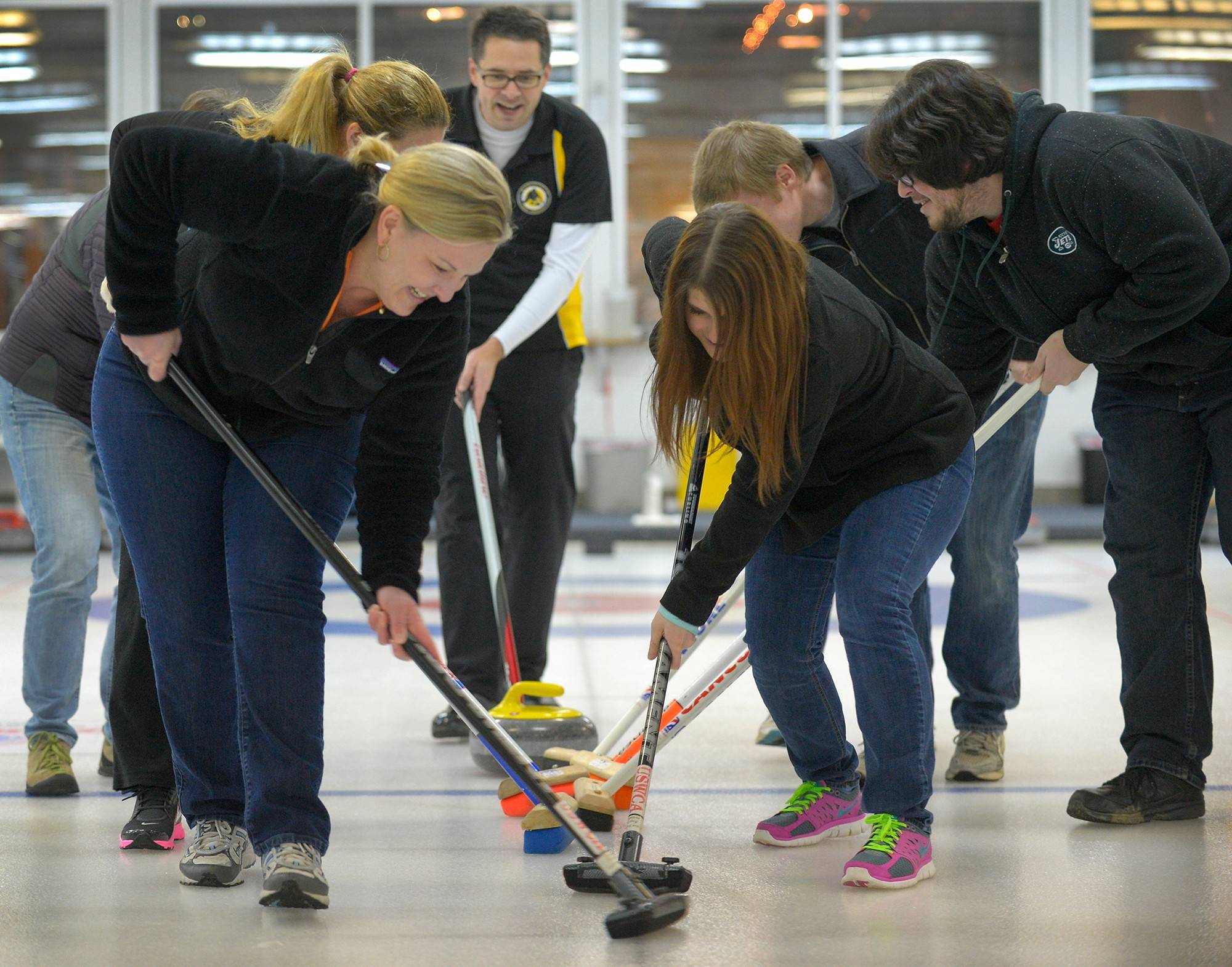 Potomac Curling Club member Todd Humora, rear, directs a group of sweeping novices at the National Capital Curling Center in Laurel, Md.