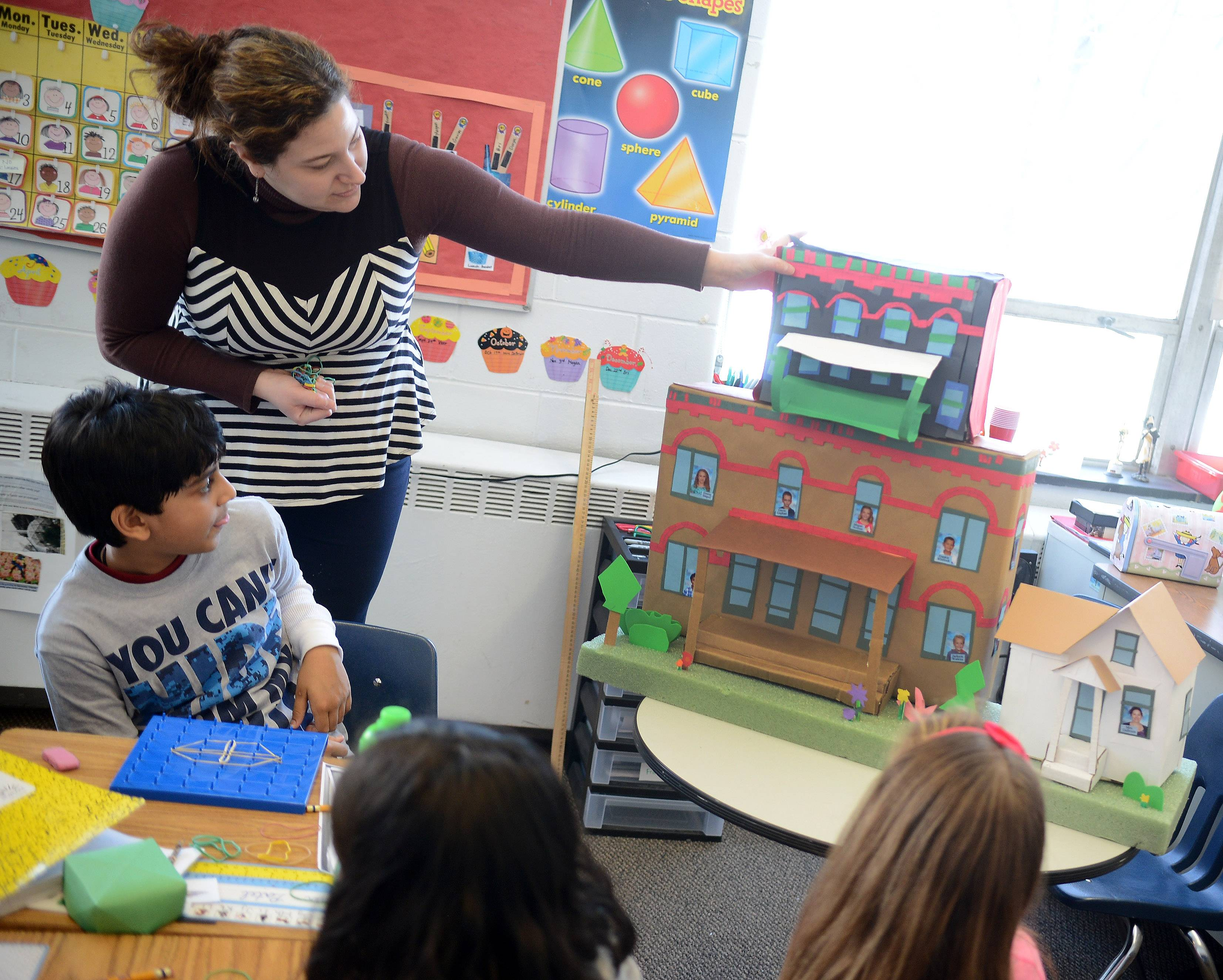 Elgin Academy second-grade teacher Ellen DeBruin arranges a class project showcasing Elgin-style architecture. The school is celebrating the 175th anniversary of its charter this month.