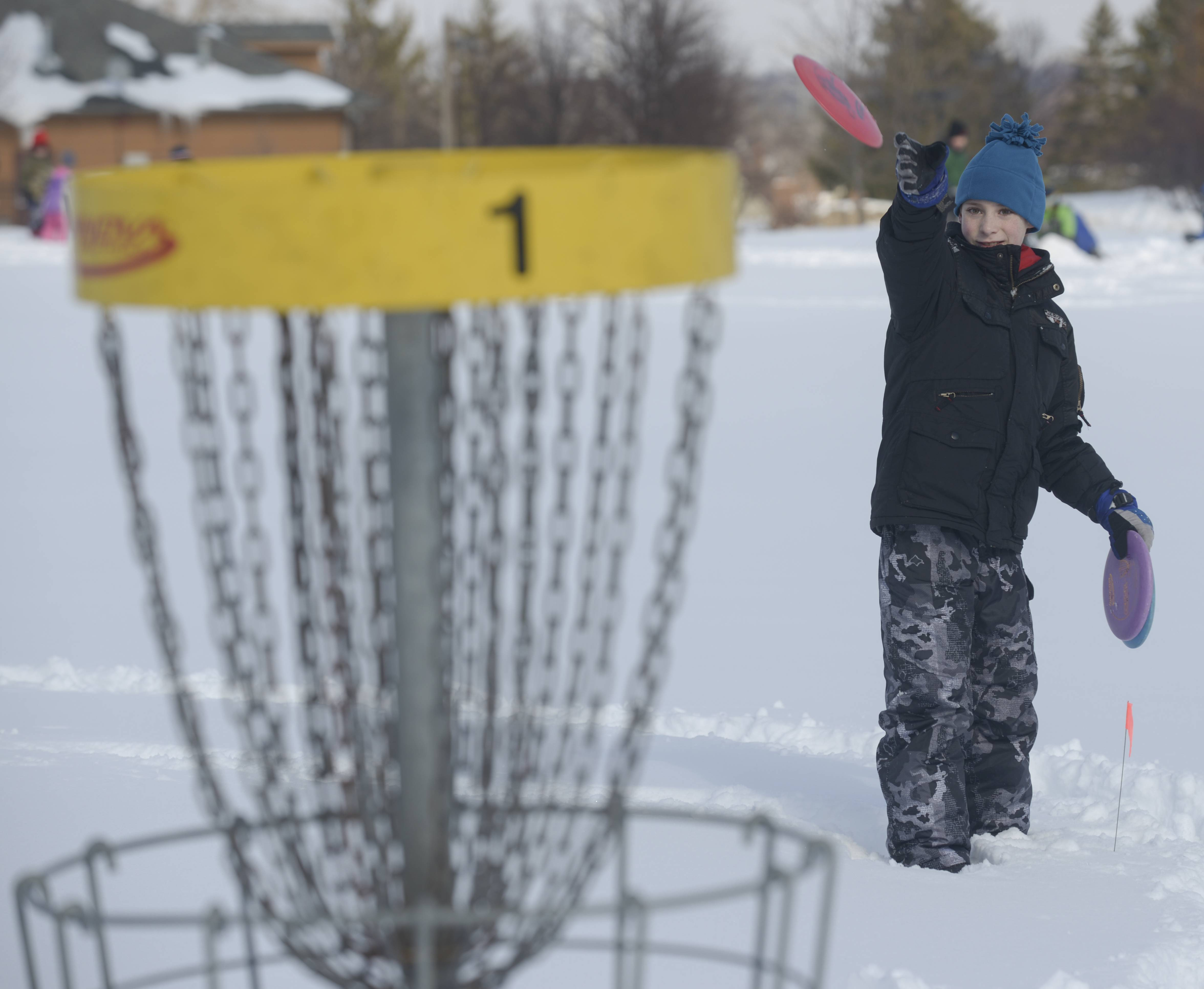 Joey Valli, 10, of Glen Ellyn tries snowy Disc Golf during the Glen Ellyn Park District's 2nd annual Arctic Blast event at Maryknoll Park on Sunday. The event also featured a snowball toss, snowman building and Chilly Paddle Tennis.