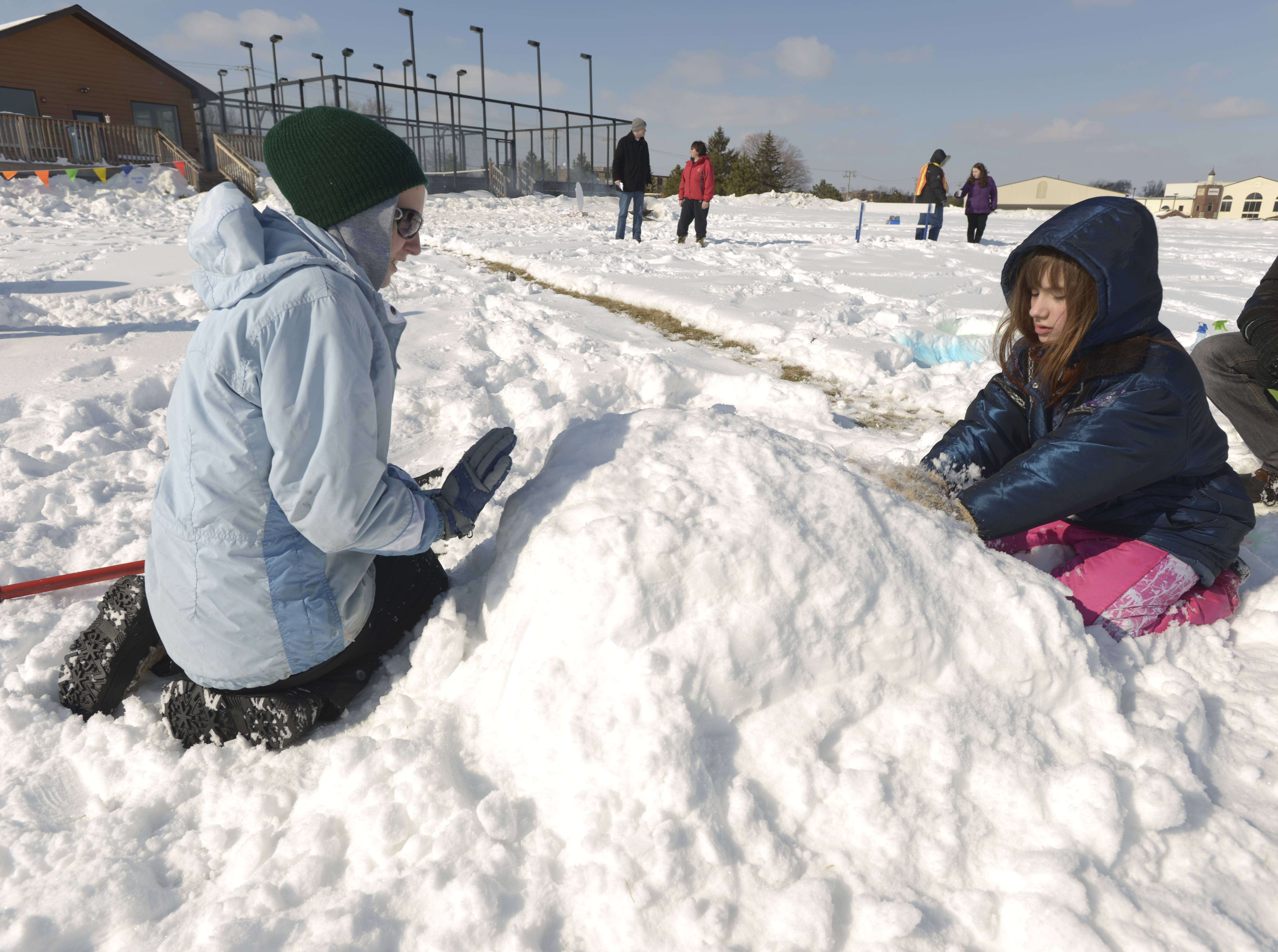 Kristine Jirsa and Tessa-Kay Stahulak, 11, of Wheaton work on building a Mickey Mouse snowman Sunday during the Glen Ellyn Park District's 2nd annual Arctic Blast event at Maryknoll Park.