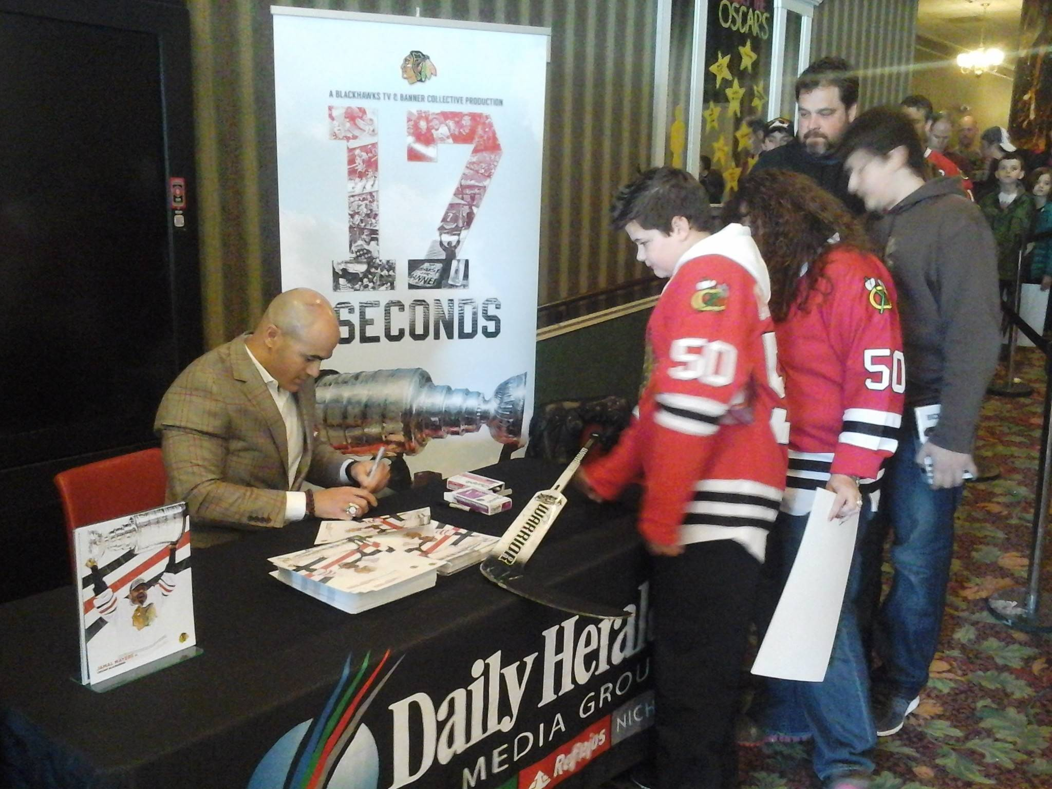 "Hockey fan Adam Rickert receives an autograph Sunday from Jamal Mayers after Sunday's screening of ""17 Seconds"" at the Fox Lake Theatre. It was the third of four screenings the Daily Herald and the Blackhawks partnered to present in the suburbs."