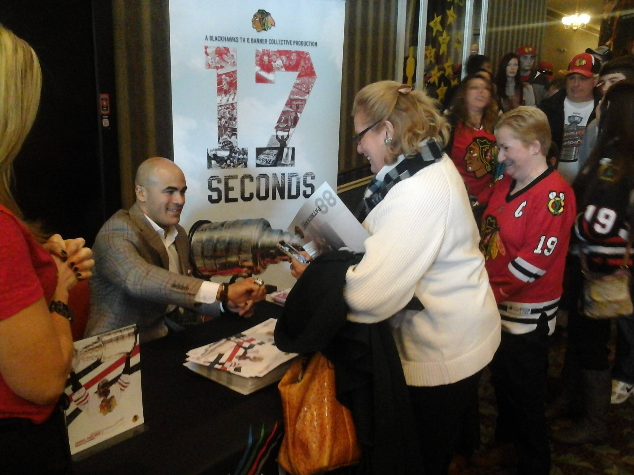 "Gail Brooks of Bull Valley exchanges a few words with former Blackhawks forward Jamal Mayers following the screening of ""17 Seconds"" at the Fox Lake Theatre on Sunday. It was the third of four screenings the Daily Herald and the Blackhawks partnered to present in the suburbs."