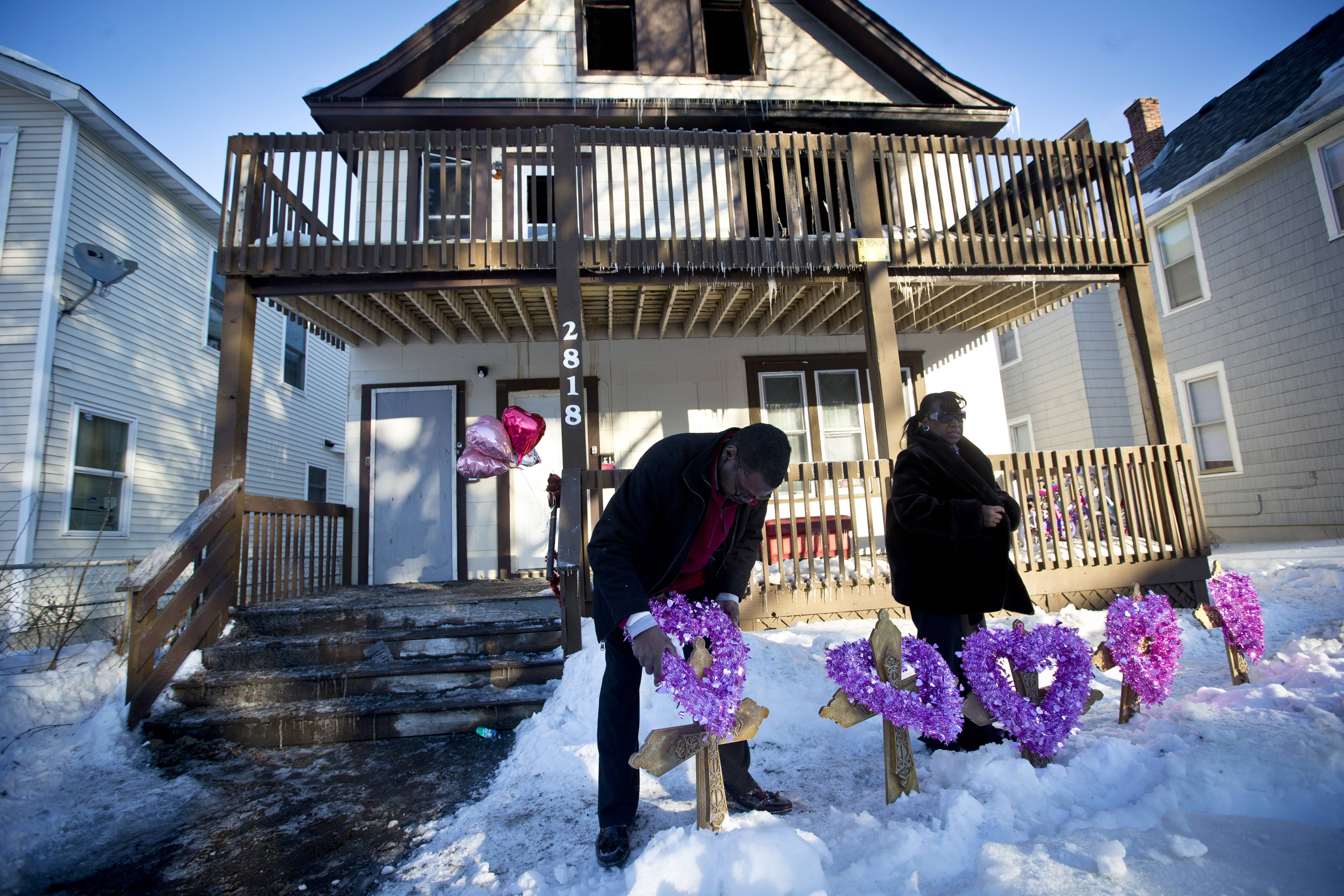 John Martin and Helen Williams put five crosses and wreaths in front of the home where people were killed in a house fire on Friday in Minneapolis. The fire killed five people, including at least three children, and injured several others, officials said.