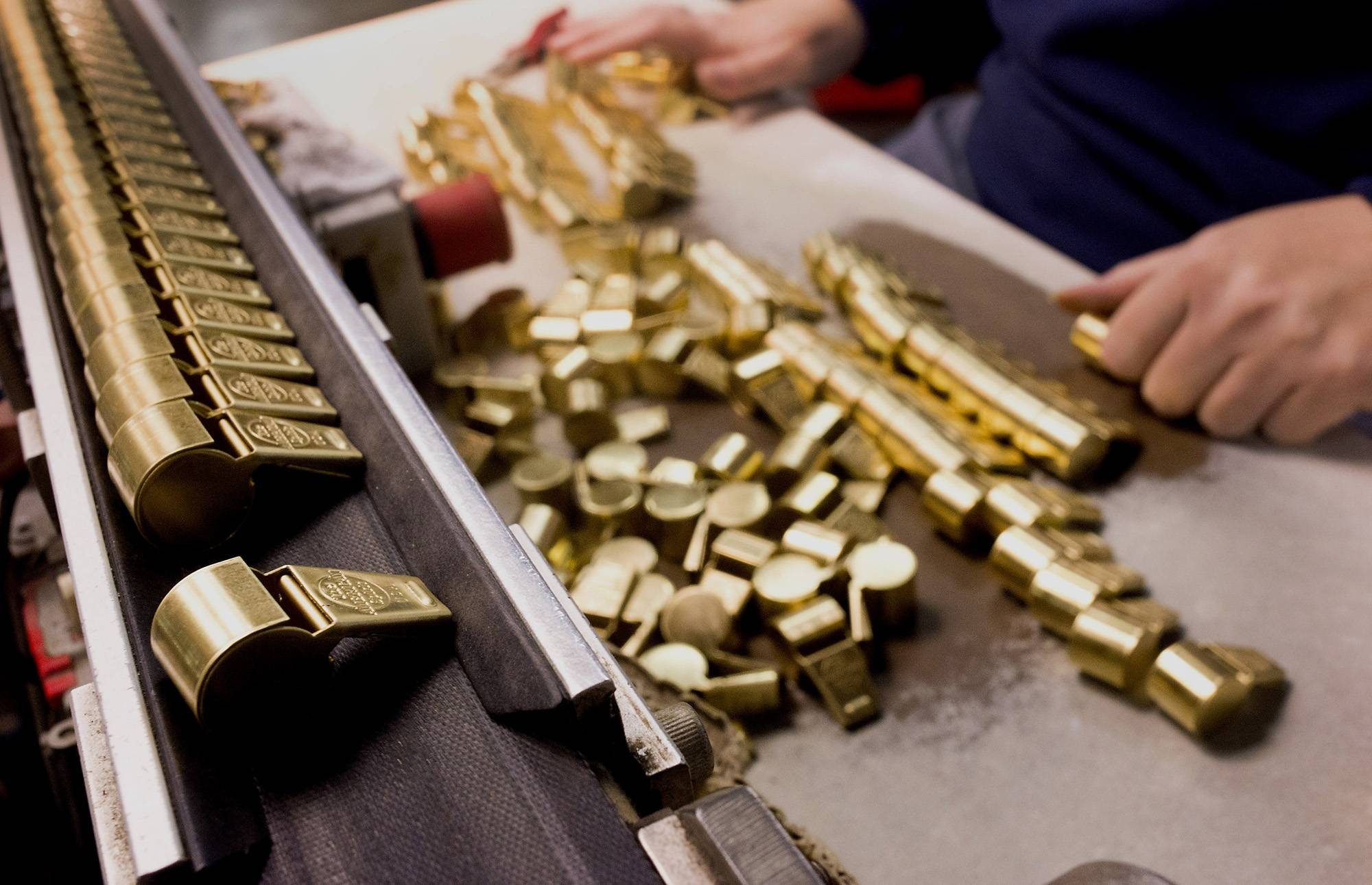 A worker lines brass pieces of whistles onto a conveyor belt for the soldering machine at the American Whistle Corp. factory in Columbus, Ohio, on Feb. 3. Amercians are holding multiple jobs to earn extra income in a still-erratic job market, to supplement wages or to get paid for time they spend on hobbies or interests. About 4.9 percent of working U.S. adults have more than one job, with about half holding a full-time and a part-time position.