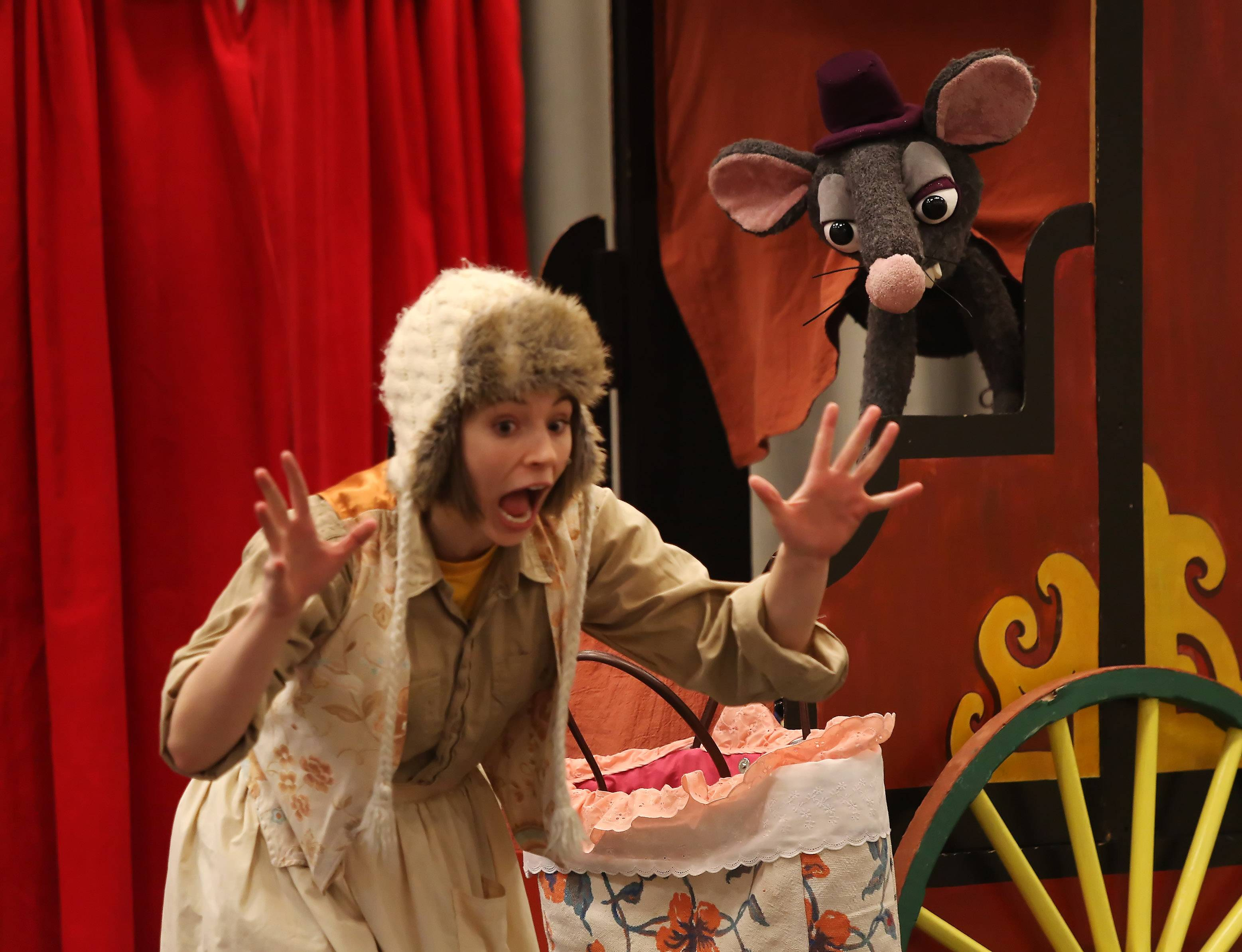 "Beula Bugbottom, played by Emily Marsh, is surprised by a talking rat during the ""Enchanted World"" show Sunday by the Madcap Puppets at the Des Plaines Public Library. Traveling showman Silas B. Thislewig, played by Chance Kilgour, entertained children and families with fairy tales using giant puppets."