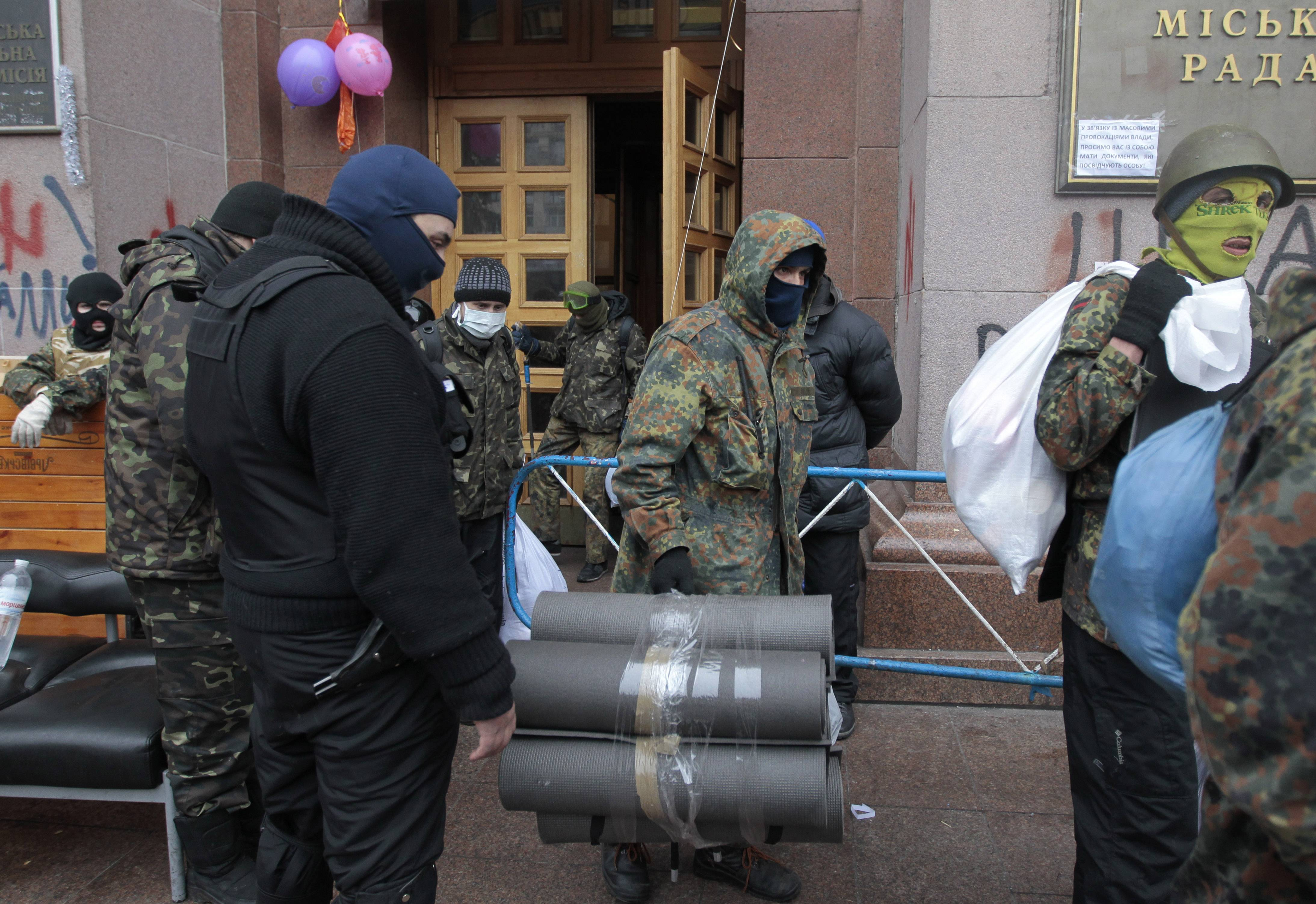 Opposition supporters leave Kiev City Hall in Kiev, Ukraine on Sunday. Anti-government demonstrators in Ukraine's capital ended their nearly three-month occupation of Kiev City Hall on Sunday as promised in exchange for the release of all jailed protesters. But tensions remained high as hundreds stayed outside the building, vowing to retake it if the government fails to drop all criminal charges against the protesters.