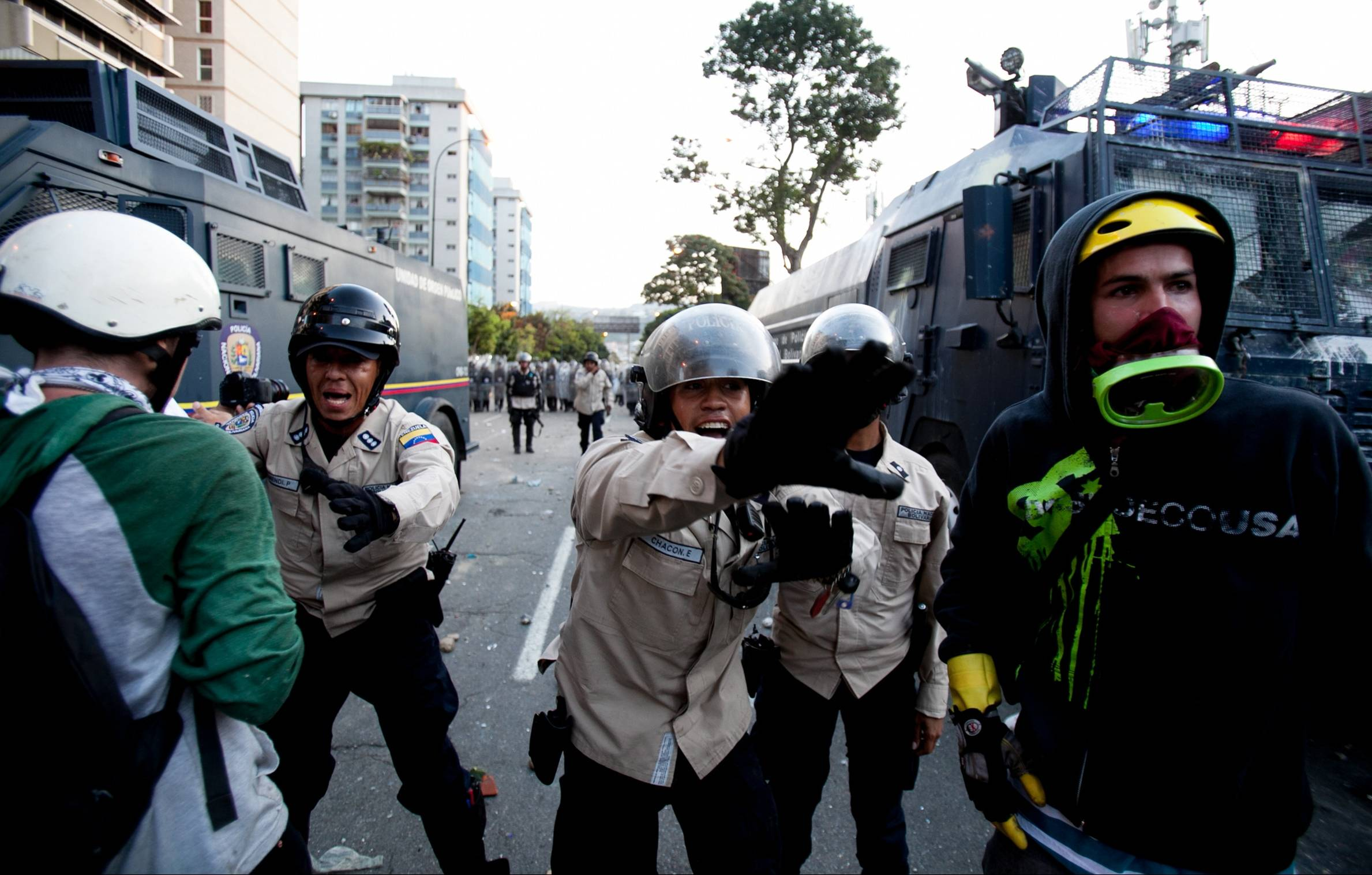 National Bolivarian Police officers yell at demonstrators Saturday to leave the area, in Caracas, Venezuela.