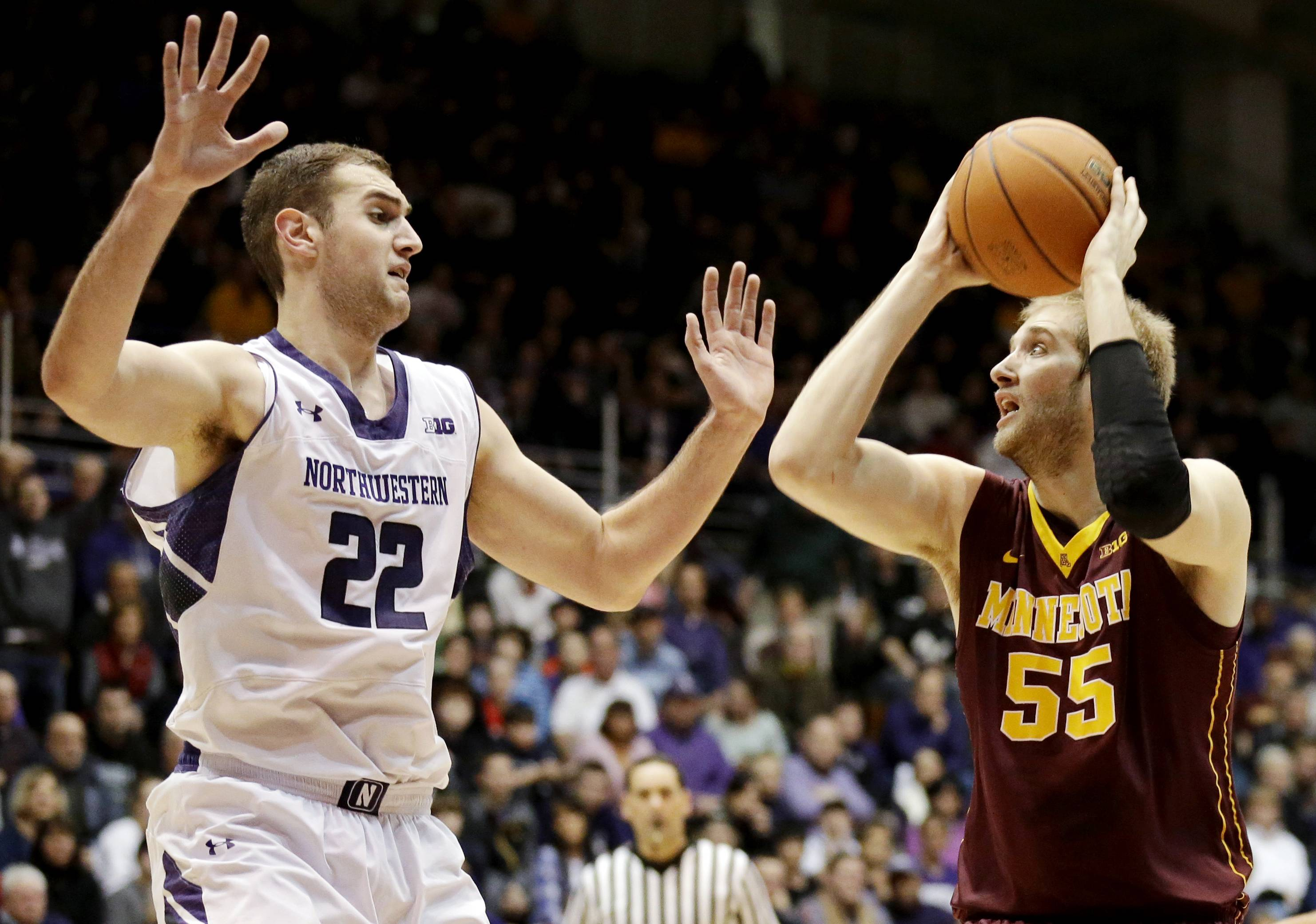 Minnesota center Elliott Eliason, right, looks to the basket against Northwestern center Alex Olah during the first half of an NCAA college basketball game in Evanston, Ill., Sunday, Feb. 16, 2014.