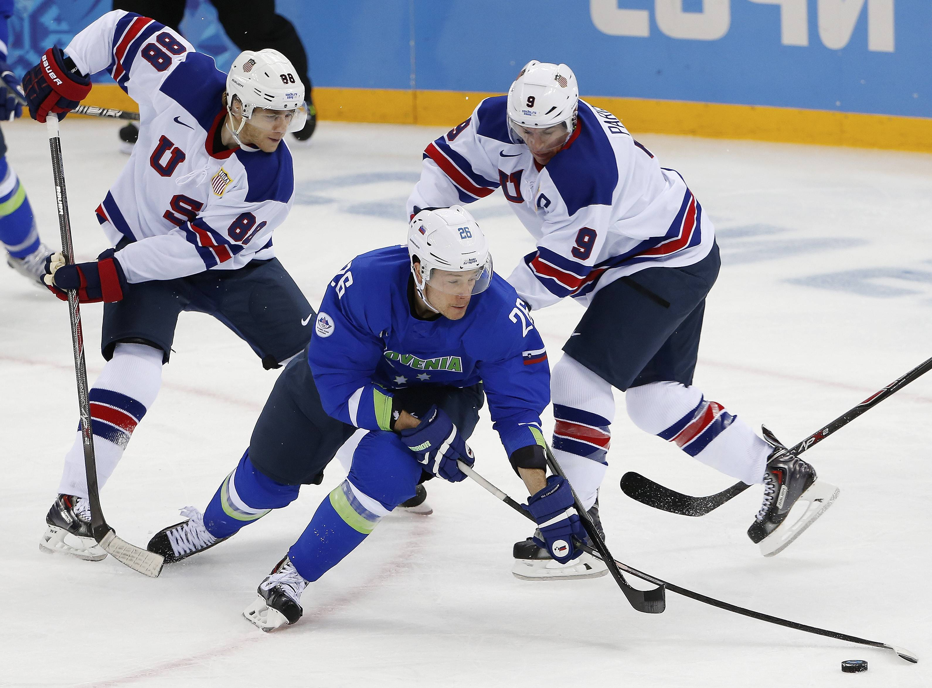 Team USA forwards Patrick Kane, left, and Zach Parise team up on Slovenia's Jan Urbas during Sunday's 5-1 victory for the Americans to close their preliminary-round games. Team USA advances to the elimination round as the No. 2 seed behind Sweden.