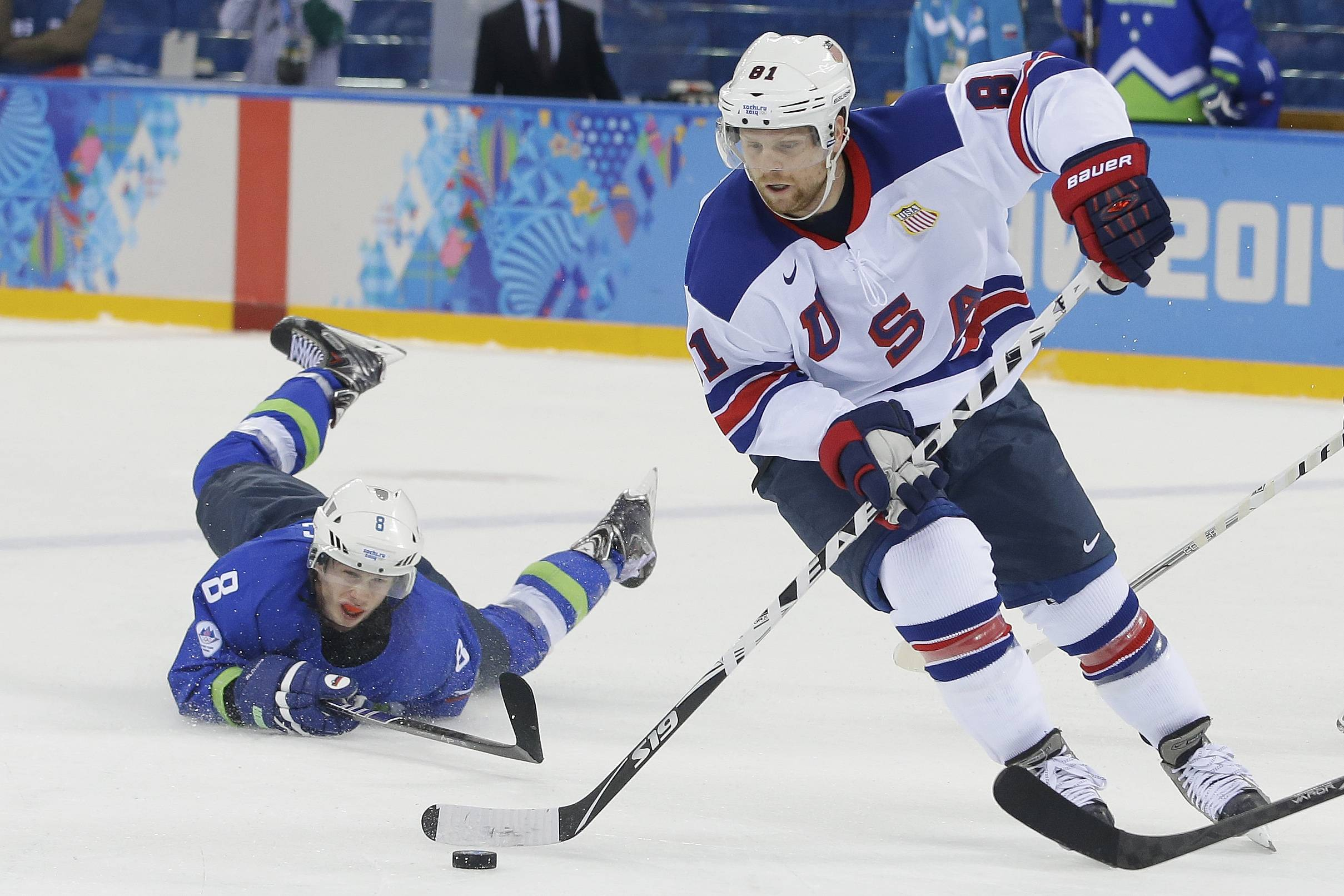 USA forward Phil Kessel take the puck away from Slovenia forward Ziga Jeglic during the 2014 Winter Olympics men's ice hockey game at Shayba Arena Sunday, Feb. 16, 2014, in Sochi, Russia.