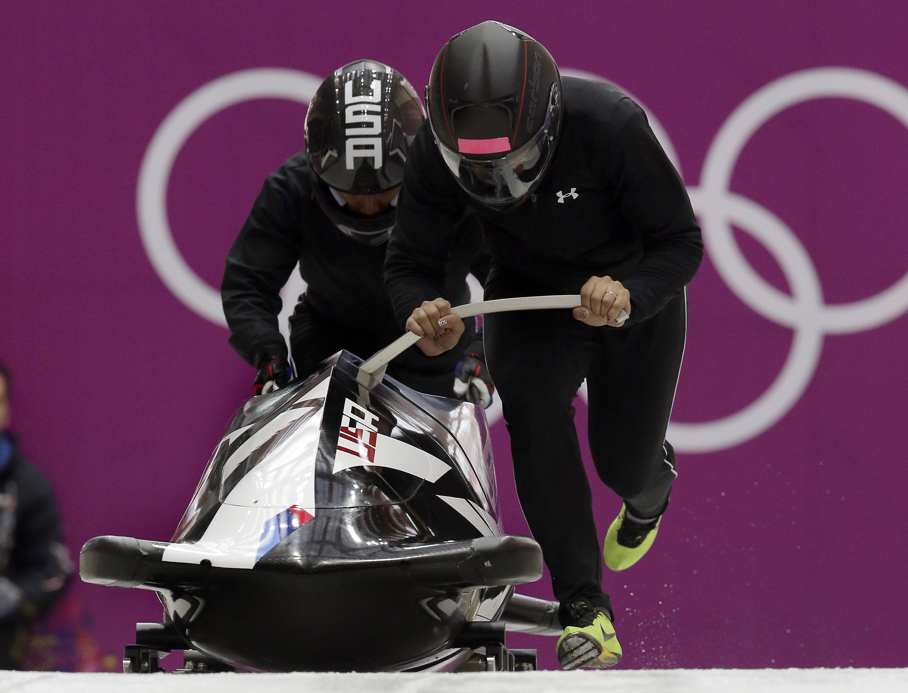 Elena Meyers, right, and Lauryn Williams of the United States start for a training session for the women's bobsled at the 2014 Winter Olympics, Sunday, Feb. 16, 2014, in Krasnaya Polyana, Russia.
