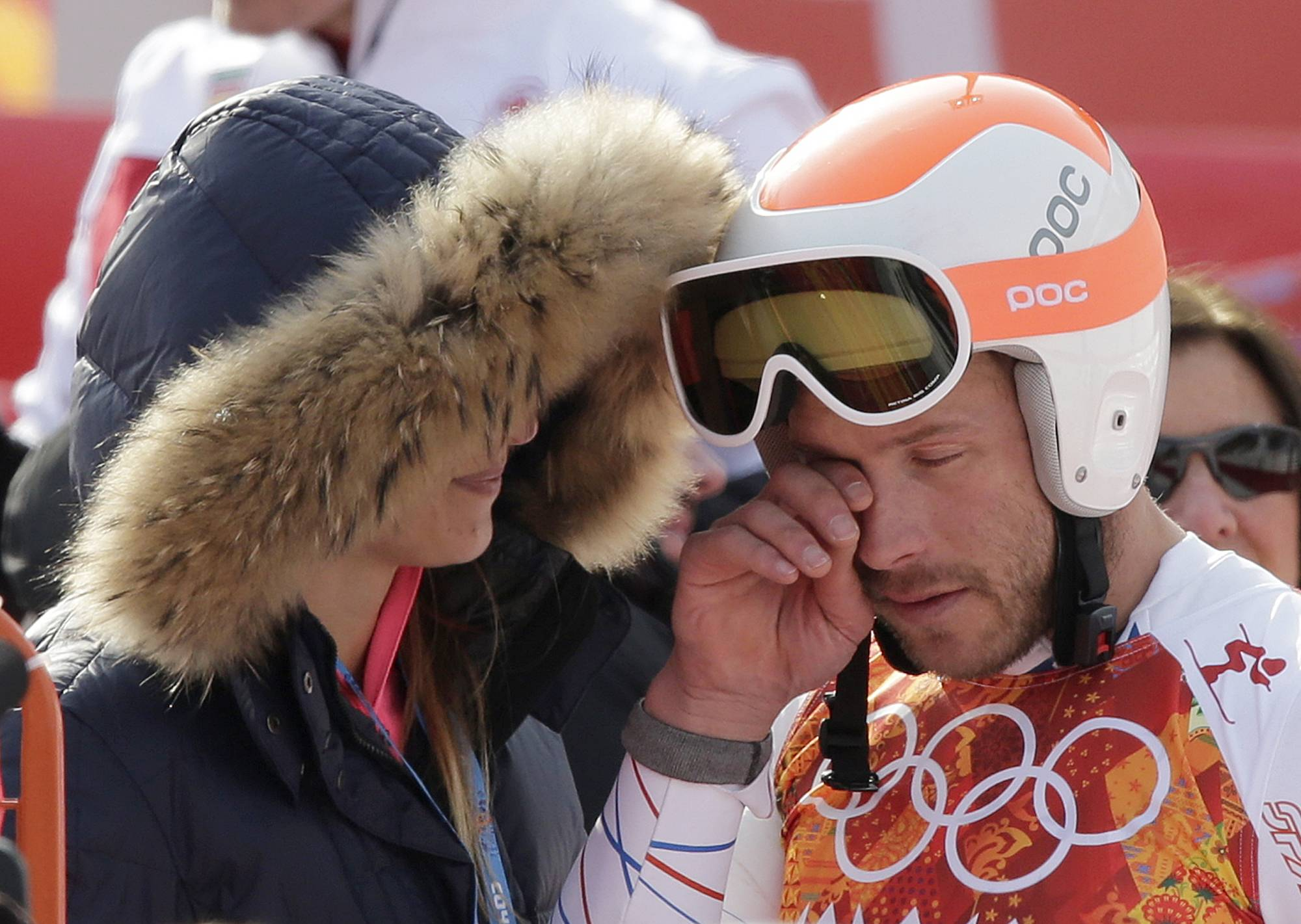 United States' Bode Miller wipes his face as he stands with his wife, Morgan, after finishing the men's super-G at the Sochi 2014 Winter Olympics, Sunday, Feb. 16, 2014, in Krasnaya Polyana, Russia.