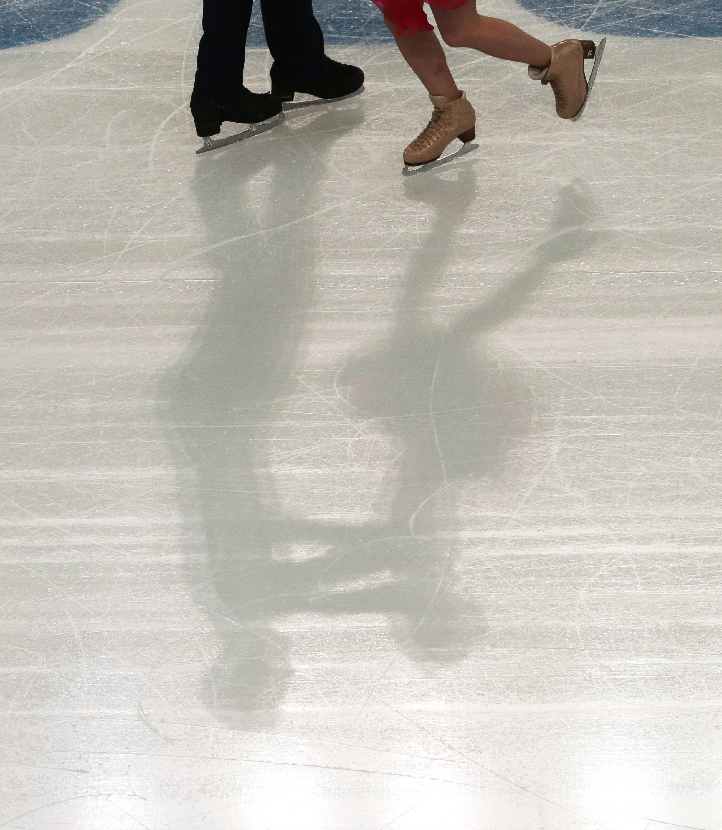 Pernelle Carron and Lloyd Jones of France cast a shadow as they compete in the ice dance short dance figure skating competition at the Iceberg Skating Palace during the 2014 Winter Olympics, Sunday, Feb. 16, 2014, in Sochi, Russia.