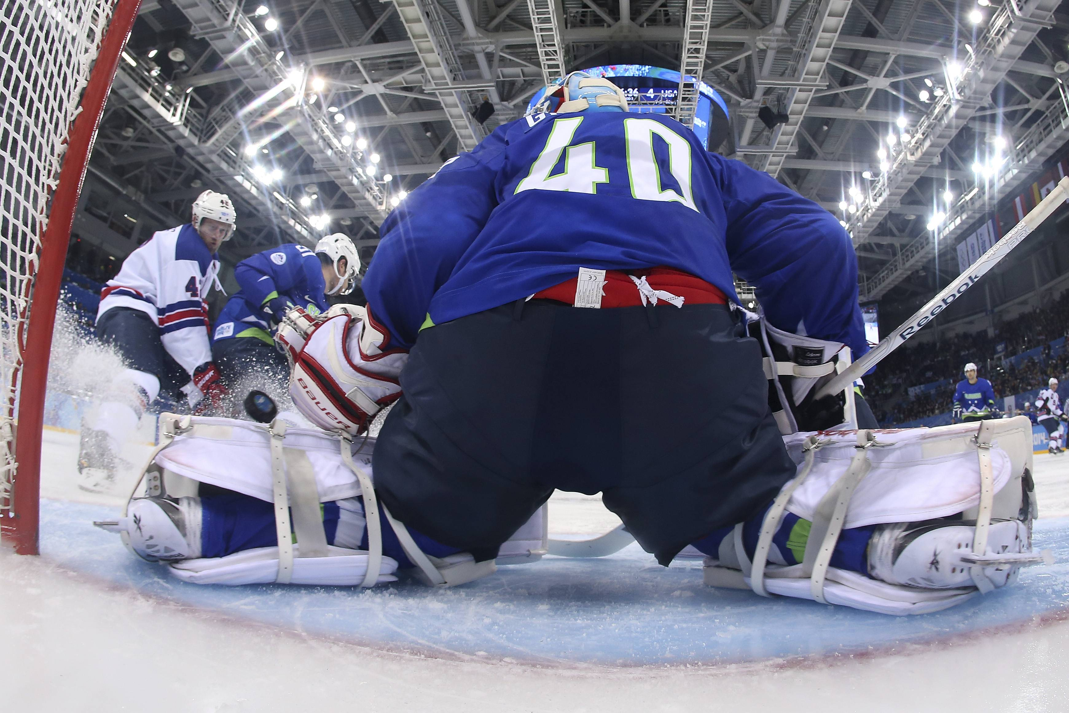 USA forward David Backes, left, fires a goal shot past Slovenia goaltender Luka Gracnar during the third period of a men's ice hockey game at the 2014 Winter Olympics, Sunday, Feb. 16, 2014, in Sochi, Russia. USA defeated Slovenia 5-1.