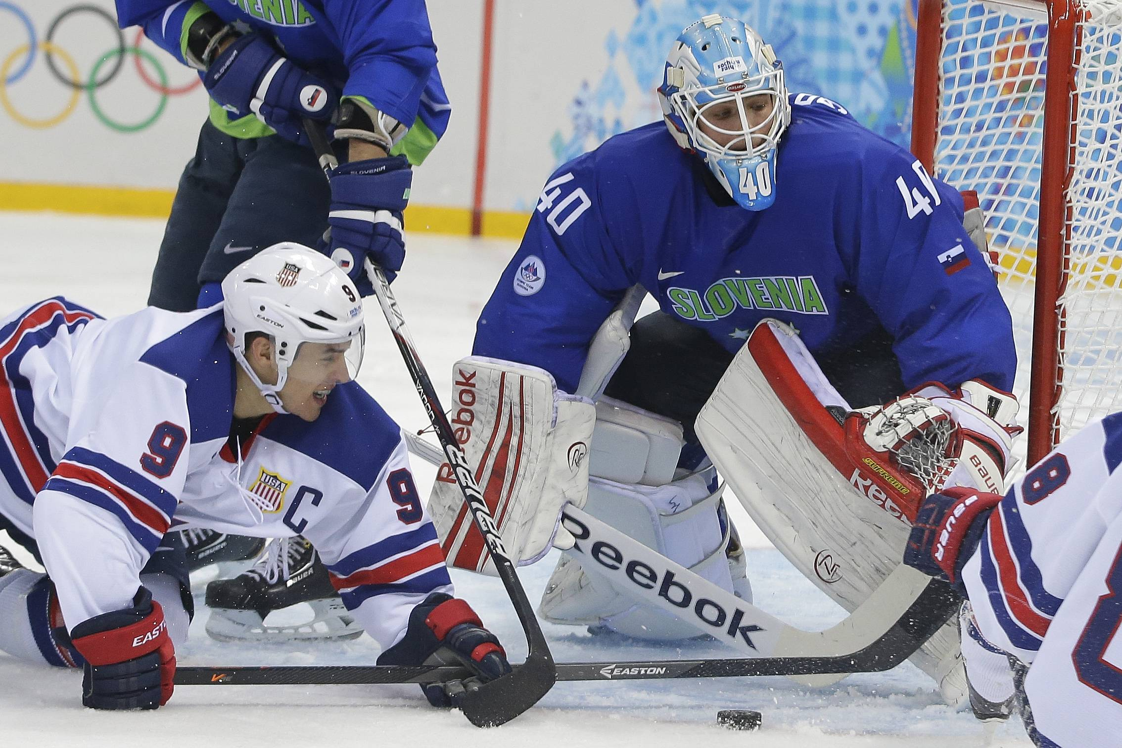 USA forward Zach Parise reaches for a loose puck in front of Slovenia goaltender Luka Gracnar during the 2014 Winter Olympics men's ice hockey game at Shayba Arena Sunday, Feb. 16, 2014, in Sochi, Russia.