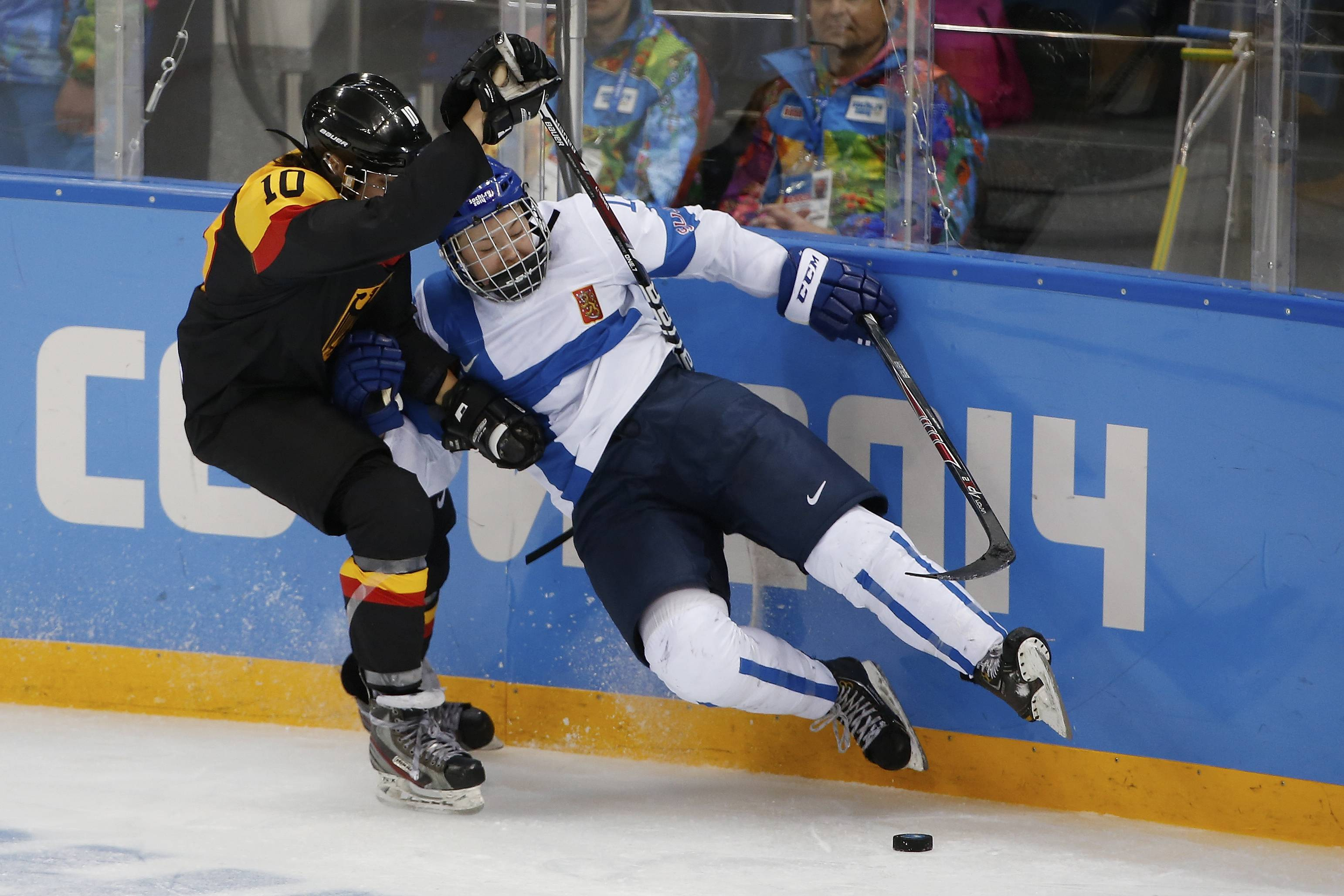 Anja Weisser of Germany knocks Minnamari Tuominen of Finland off her skates during the 2014 Winter Olympics women's ice hockey game at Shayba Arena, Sunday, Feb. 16, 2014, in Sochi, Russia. Finland defeated Germany 2-1.