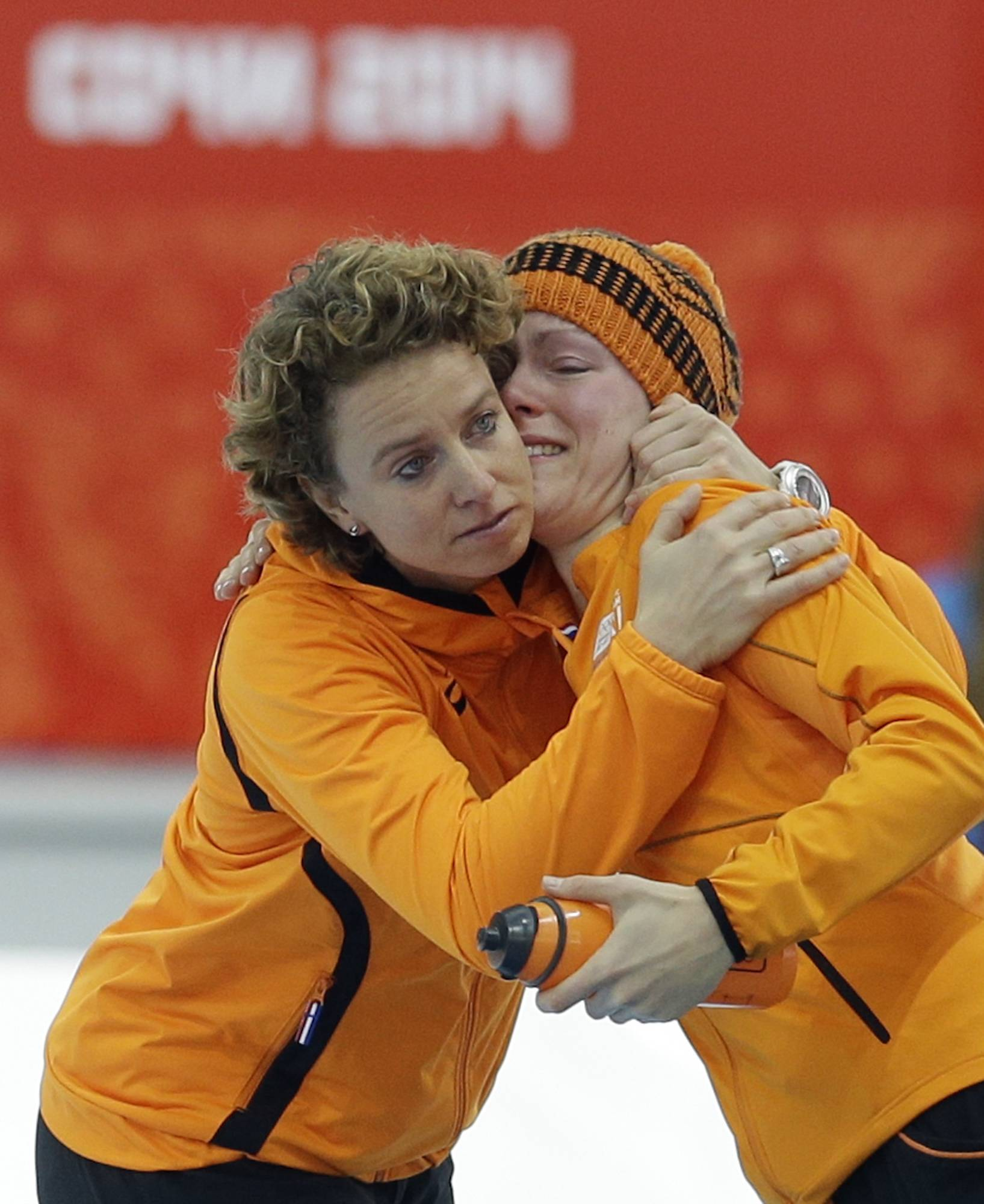 An emotional Jorien ter Mors of the Netherlands is hugged by a team member after she won gold for the women's 1,500-meter speedskating race at the Adler Arena Skating Center during the 2014 Winter Olympics in Sochi, Russia, Sunday, Feb. 16, 2014.