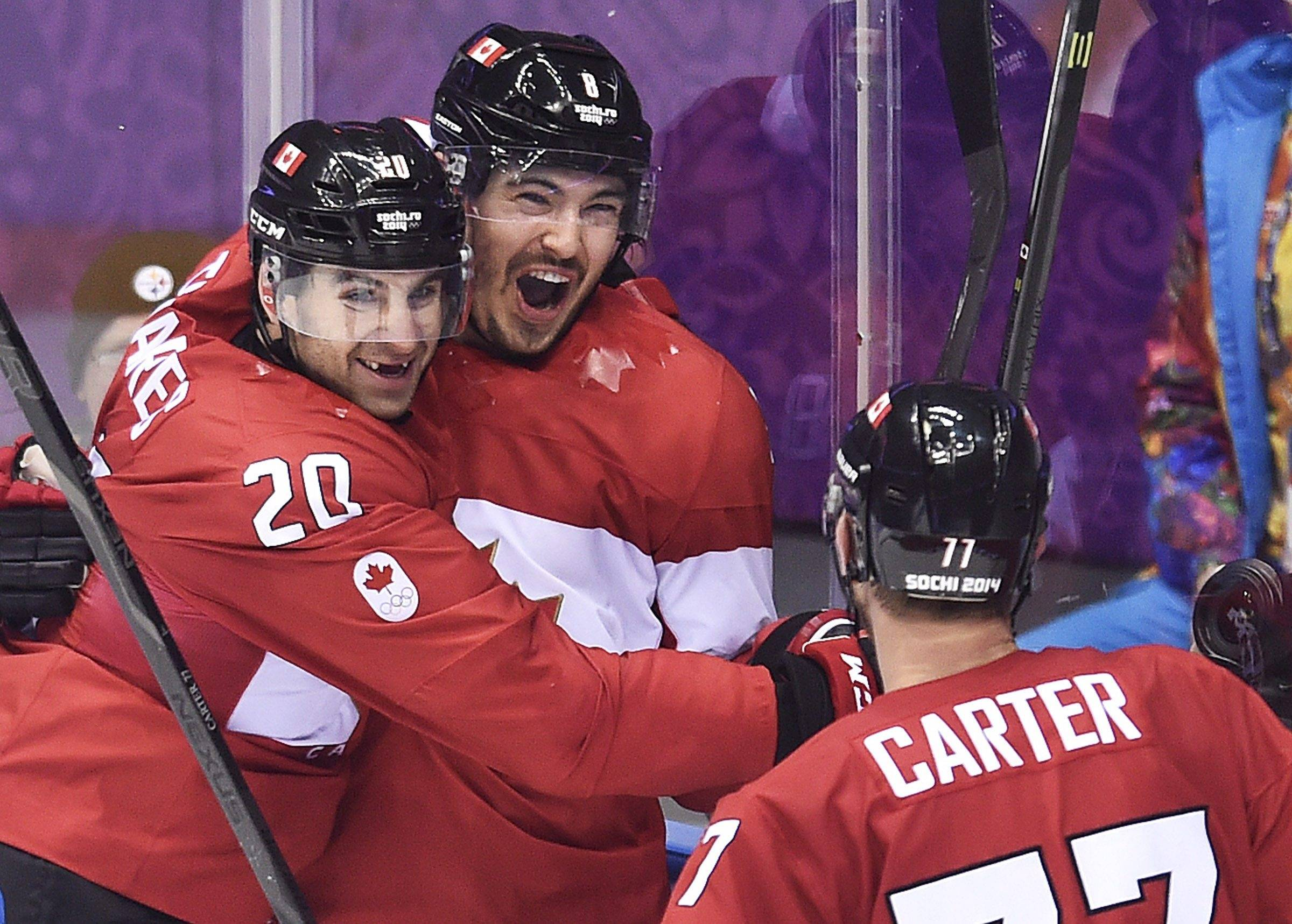 Canada defenseman Drew Doughty, center, celebrates with teammates John Tavares (20) and Jeff Carter (77) after scoring the game-winning goal in overtime against Finland in a men's ice hockey game at the Winter Olympics, Sunday, Feb. 16, 2014, in Sochi, Russia.