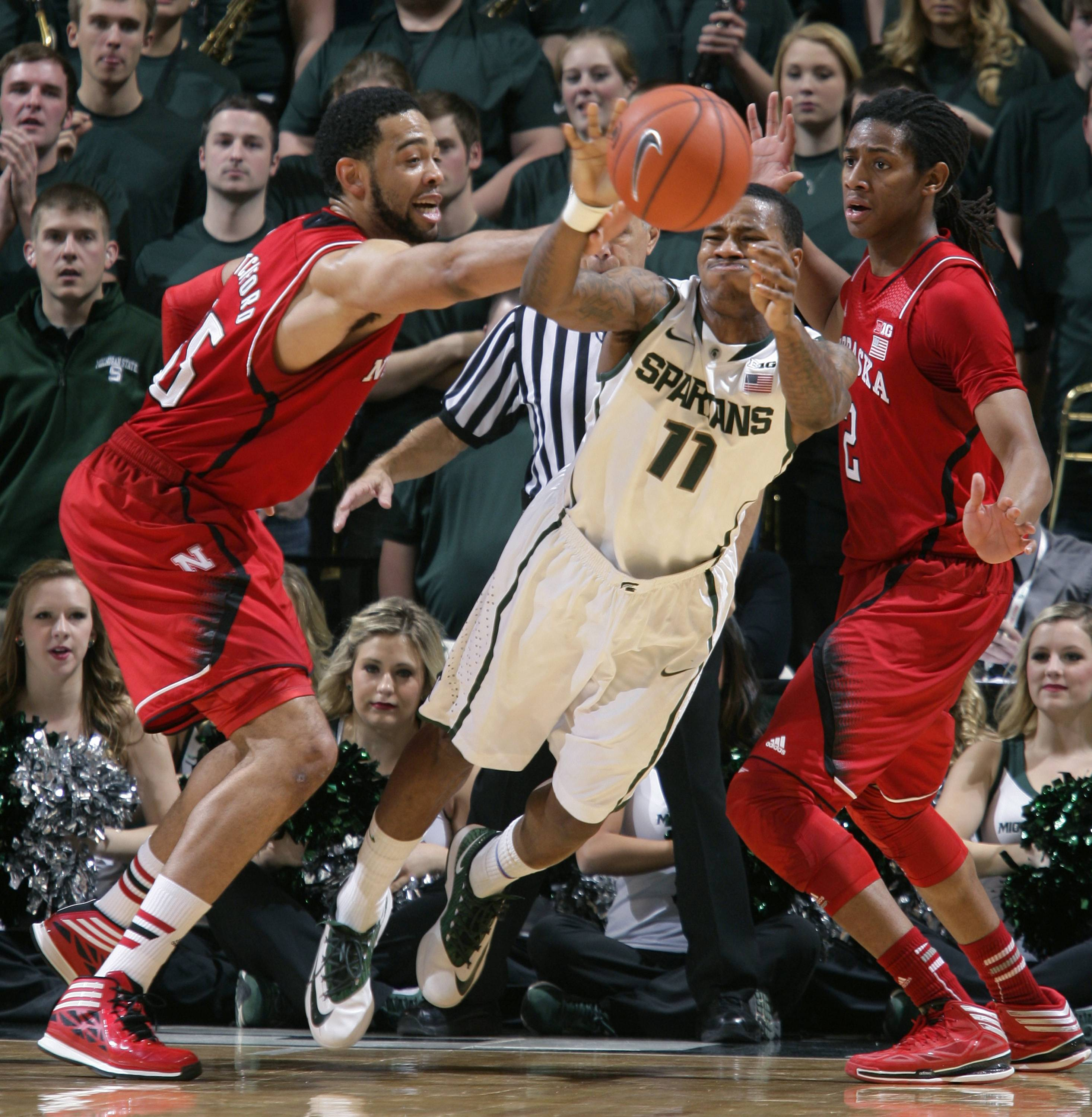 Michigan State's Keith Appling (11) tries to pass away from pressure by Nebraska's Walter Pitchford, left, and David Rivers during the first half of an NCAA college basketball game on Sunday, Feb. 16, 2014, in East Lansing, Mich.