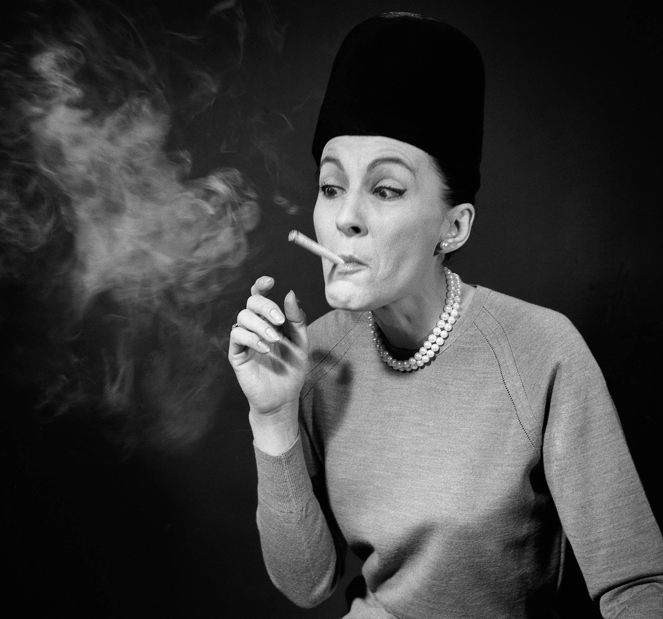 "In this April 29, 1964 file photo, etiquette expert Cathy Bauby shows how puffing a cigarette like a steam engine shows that one is behind the ""Jet Age"" and doesn't care how one looks, during a demonstration in New York. Fifty years on, health officials have begun to predict the end of cigarette smoking in America."