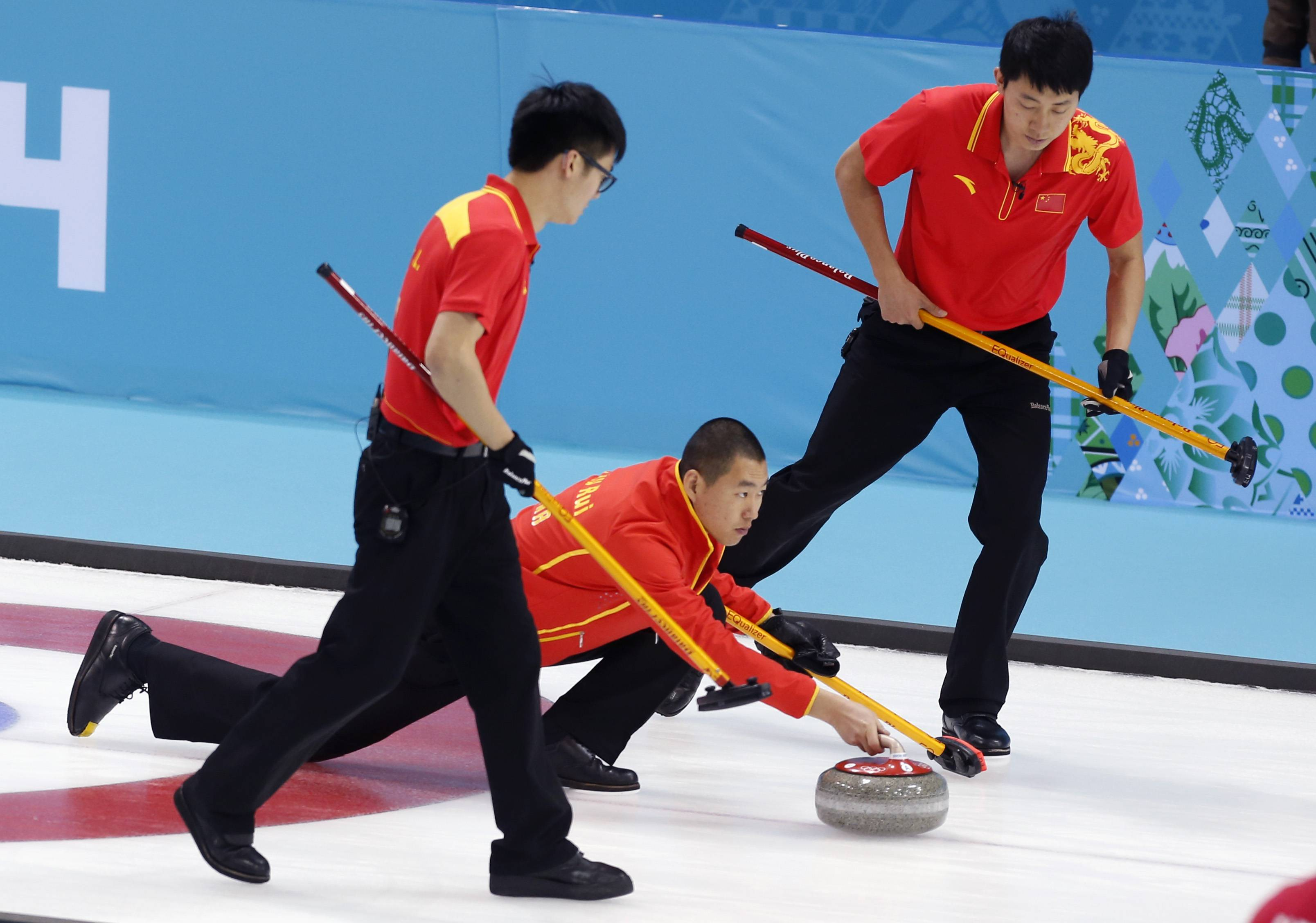 China's skip Liu Rui, center, delivers the rock to sweepers Zang Jialiang, left, and Ba Dexin Monday during men's curling competition against Britain at the 2014 Winter Olympics in Sochi, Russia.