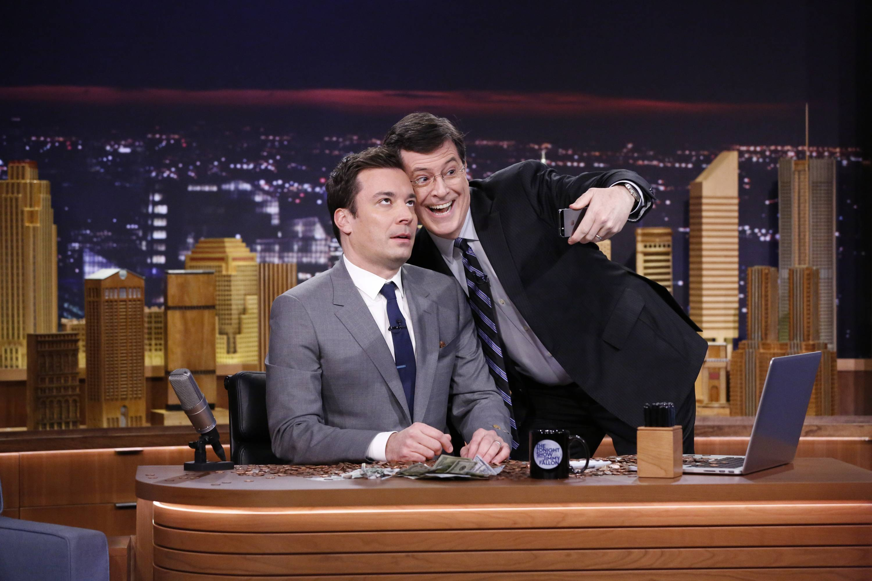 "Stephen Colbert, right, dumped pennies all over Jimmy Fallon and his desk and posed in a selfie with him during Fallon's ""The Tonight Show"" debut on Monday."